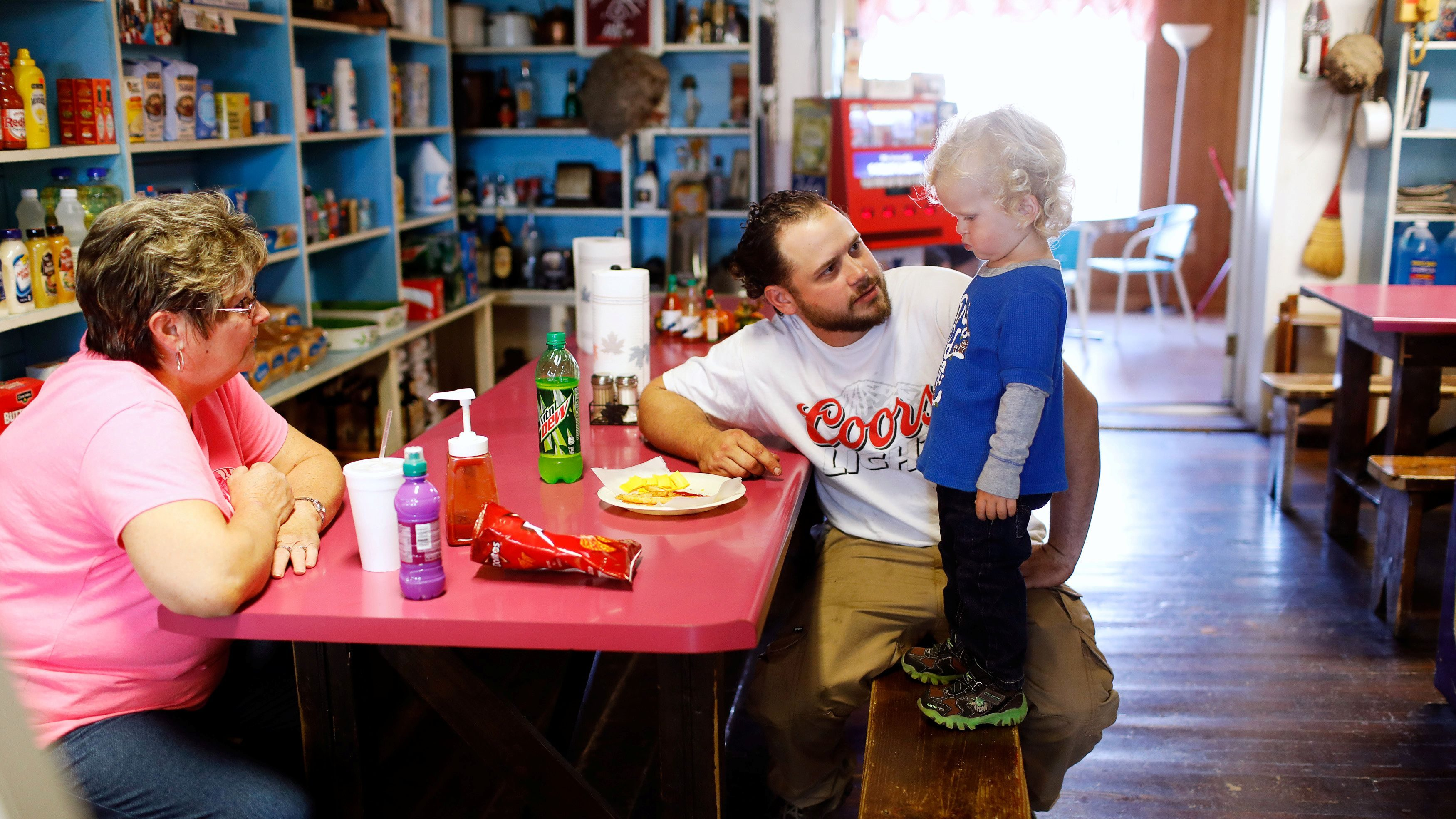 A father encourages his child to eat.