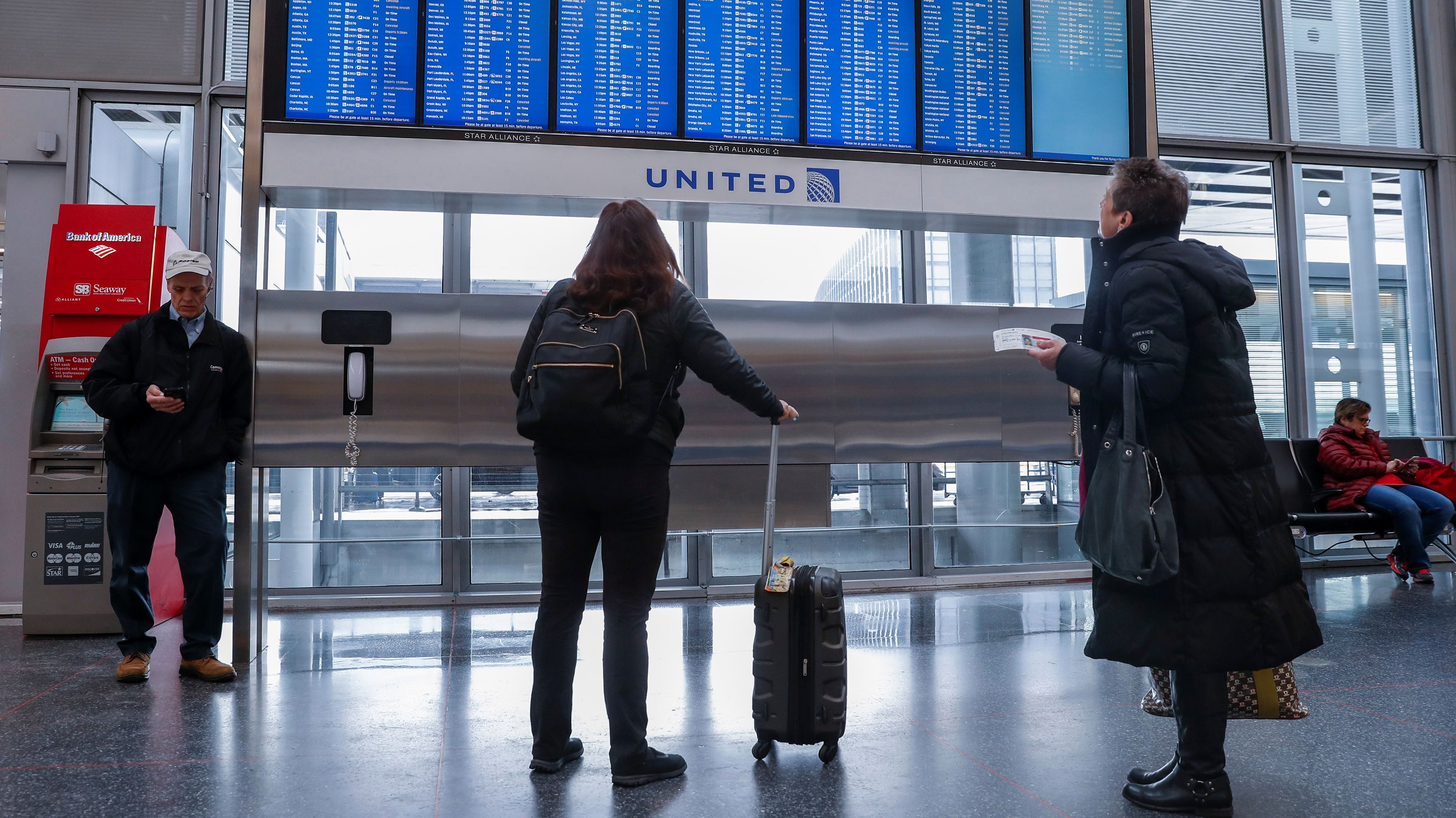 Travelers check the departure board at O'Hare International Airport in Chicago