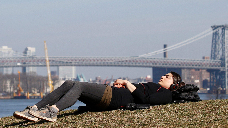 A woman naps in Brooklyn Bridge Park during unseasonably warm weather in Brooklyn, New York