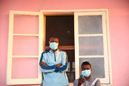 Tuberculosis patients, wearing masks to stop the spread of the disease, stand outside their ward at Chiulo Hospital, Cunene province