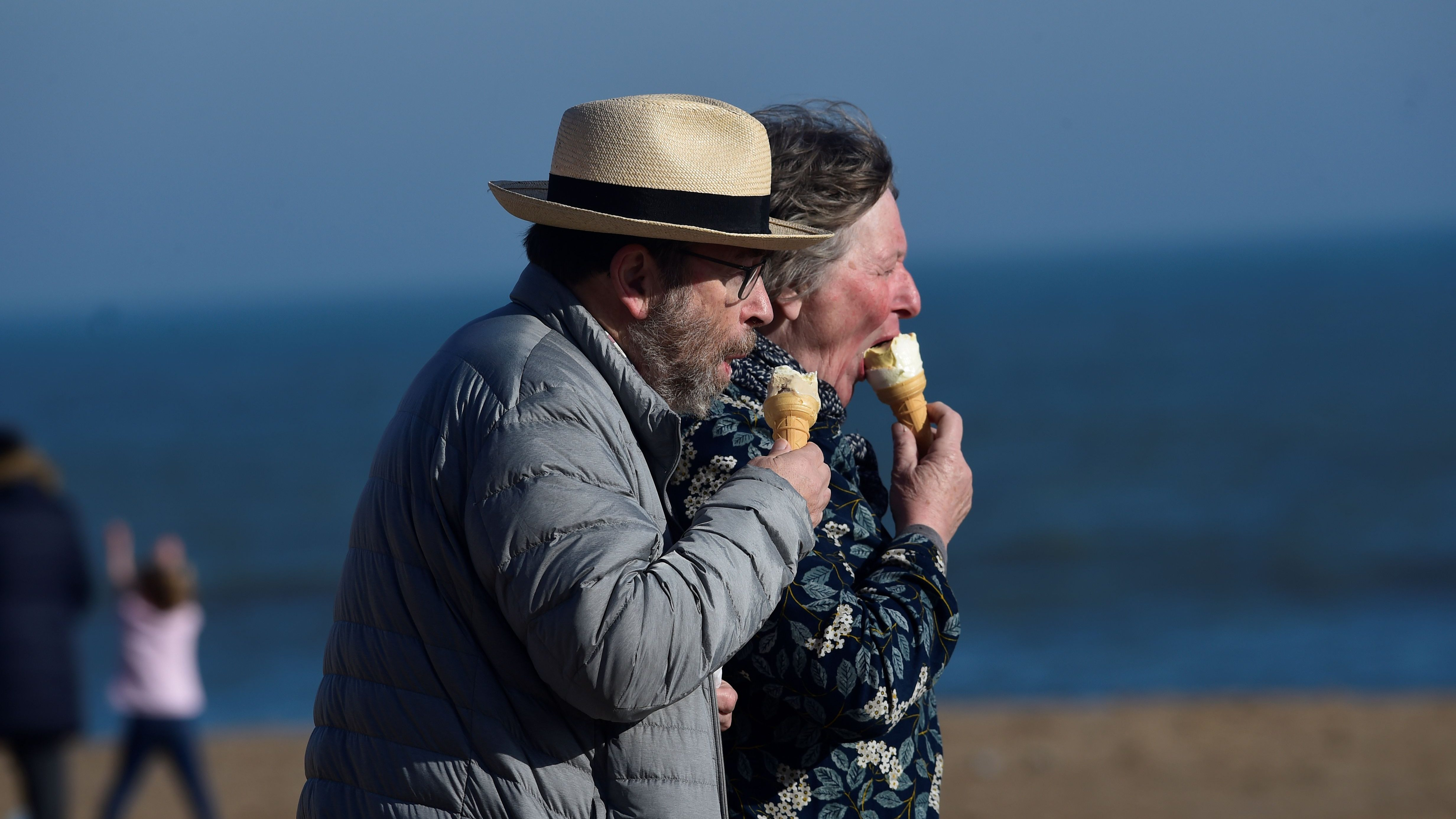 A couple eat ice-creams in the sunshine at South Beach, Tenby, Pembrokeshire, Wales, Britain