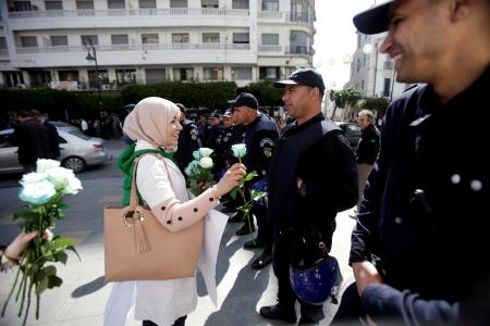 A demonstrator offers a flower to a police officer as teachers and students take part in a protest demanding immediate political change in Algiers, Algeria March 13, 2019.