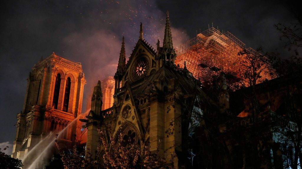 Sparks fill the air as Paris Fire brigade members spray water to extinguish flames as the Notre Dame Cathedral burns in Paris, France, April 15, 2019.
