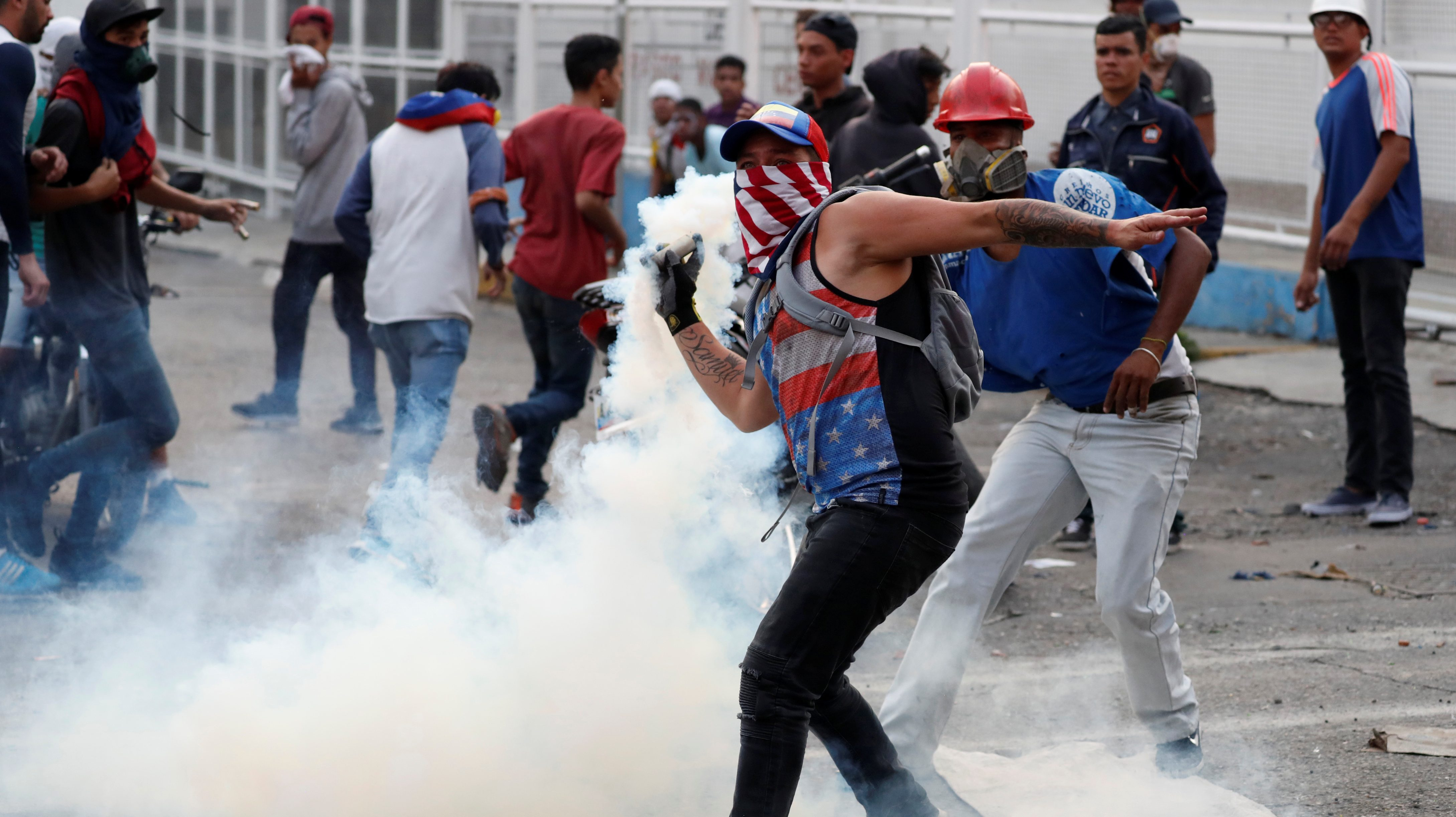 A demonstrator throws back a tear gas canister during clashes with government security forces in Caracas, Venezuela April 30, 2019.