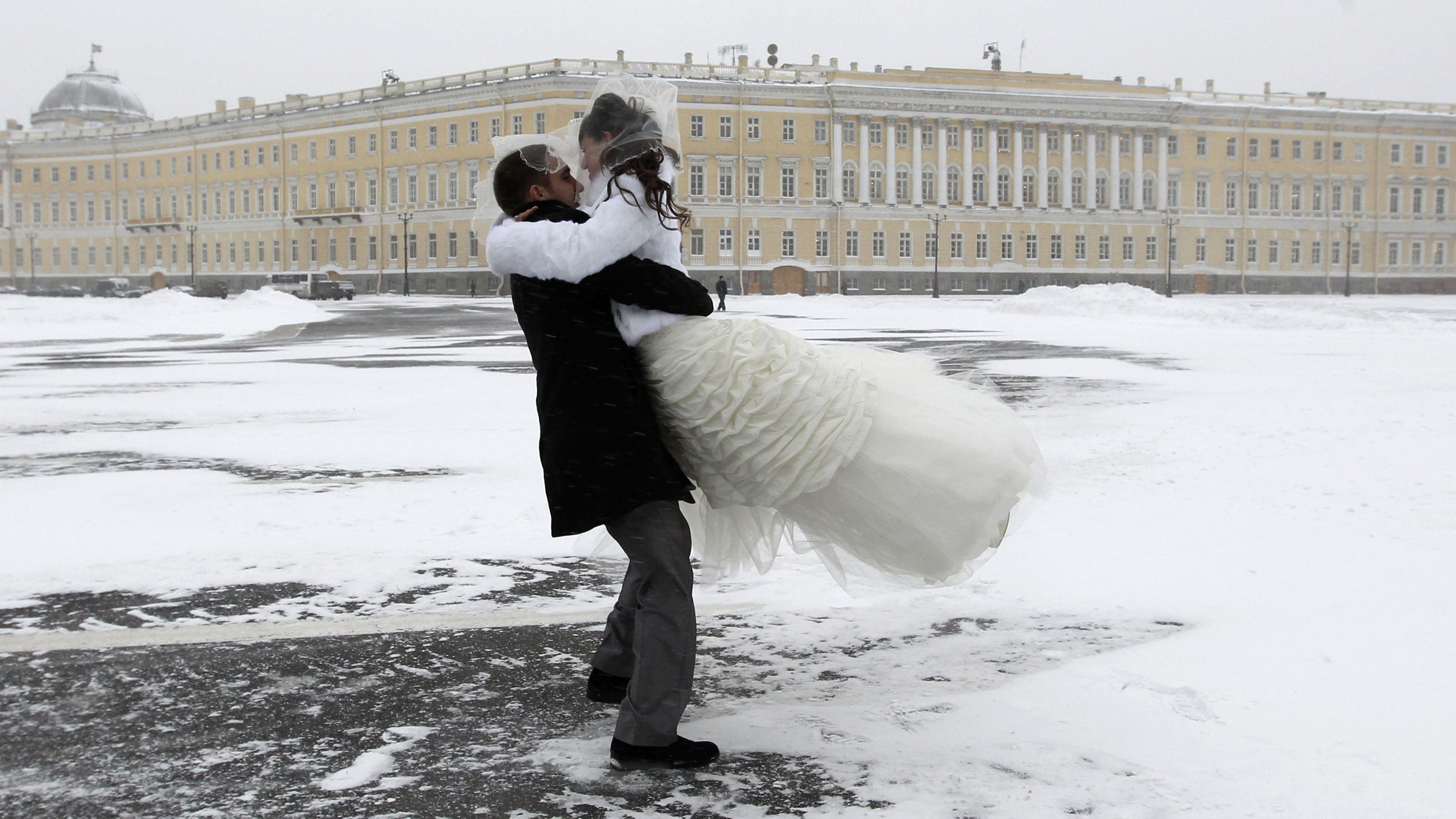 A groom carries his bride as they celebrate their wedding in the snow at Dvortsovaya Square in central St. Petersburg.