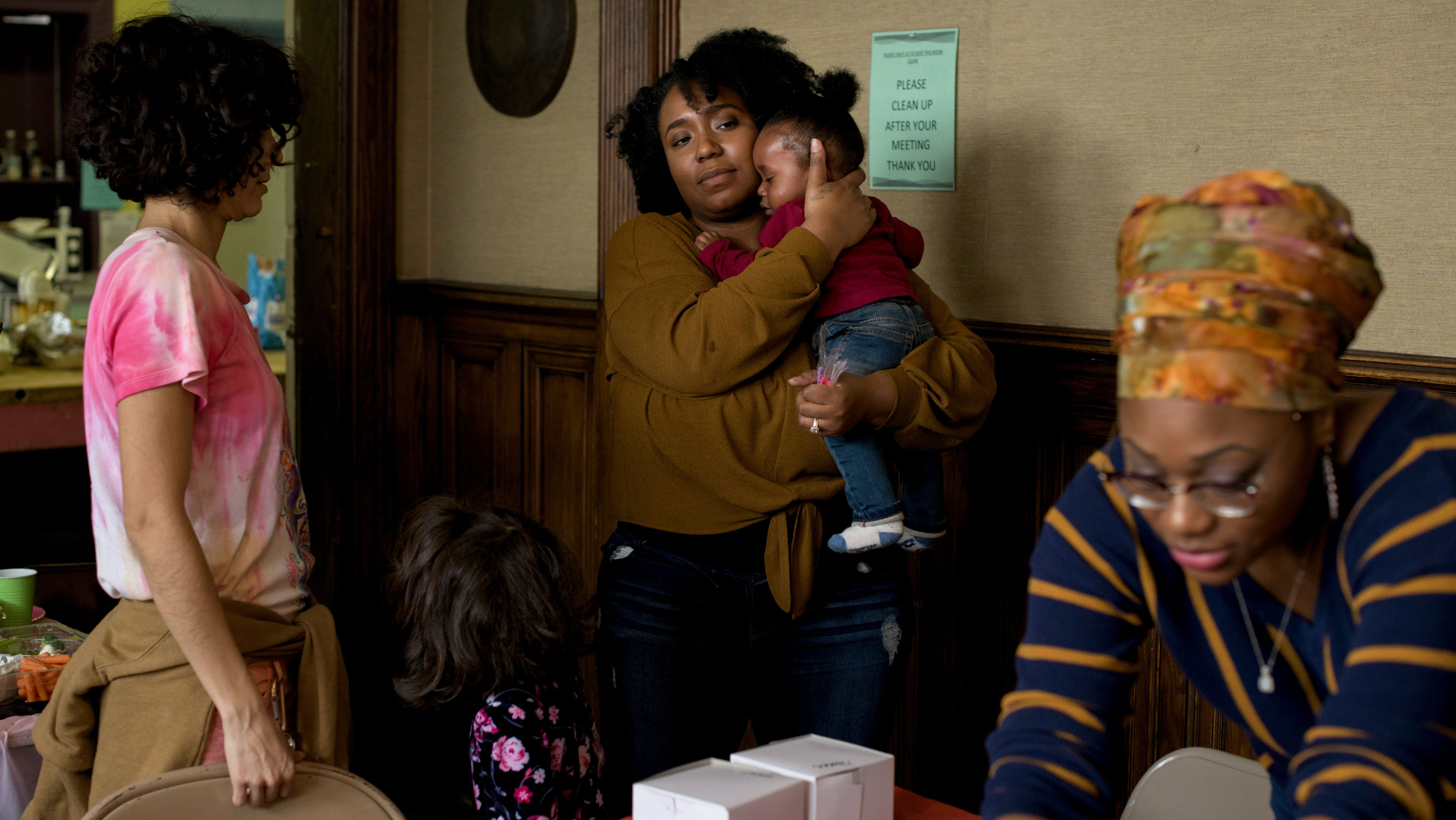 Siwatu-Salama Ra, 27, holds her 10-month-old son Zakai during her daughter Zala's 4th birthday party at the Cass Commons, the site of Siwatu's work, in Detroit, Mich., on March 24, 2019.