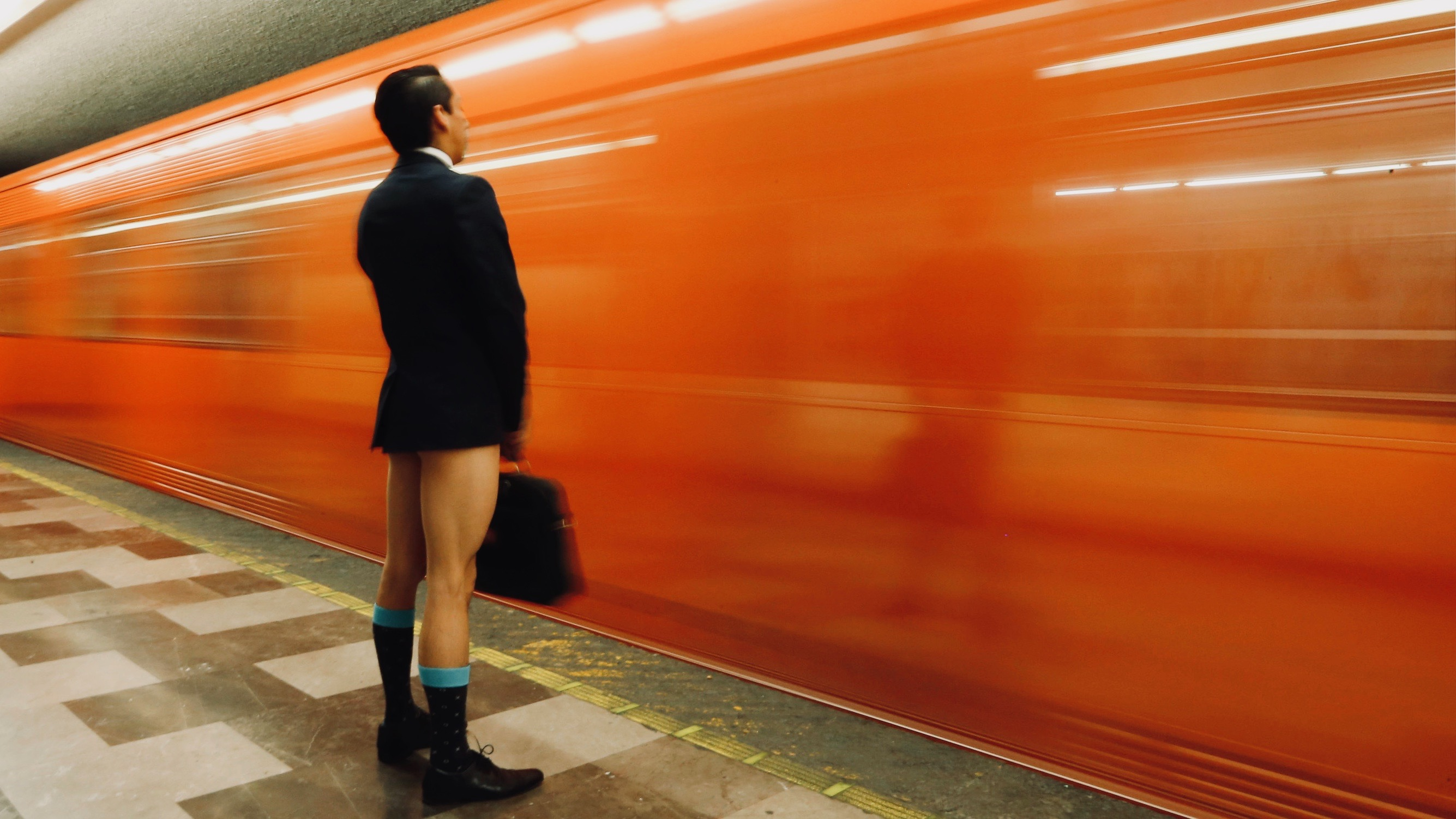 Man without pants waits for subway.