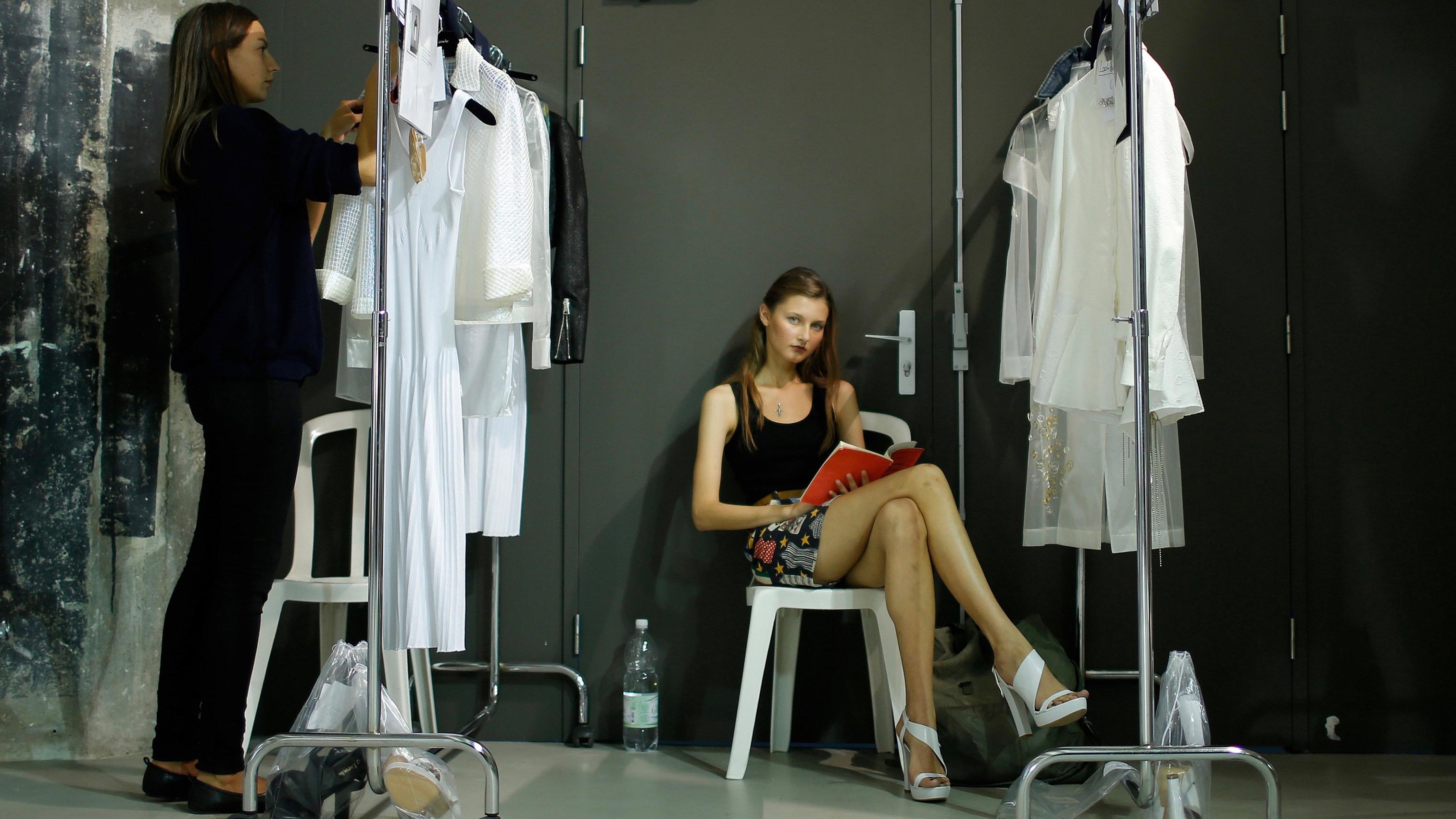 Reading backstage during Fashion Week in Paris.