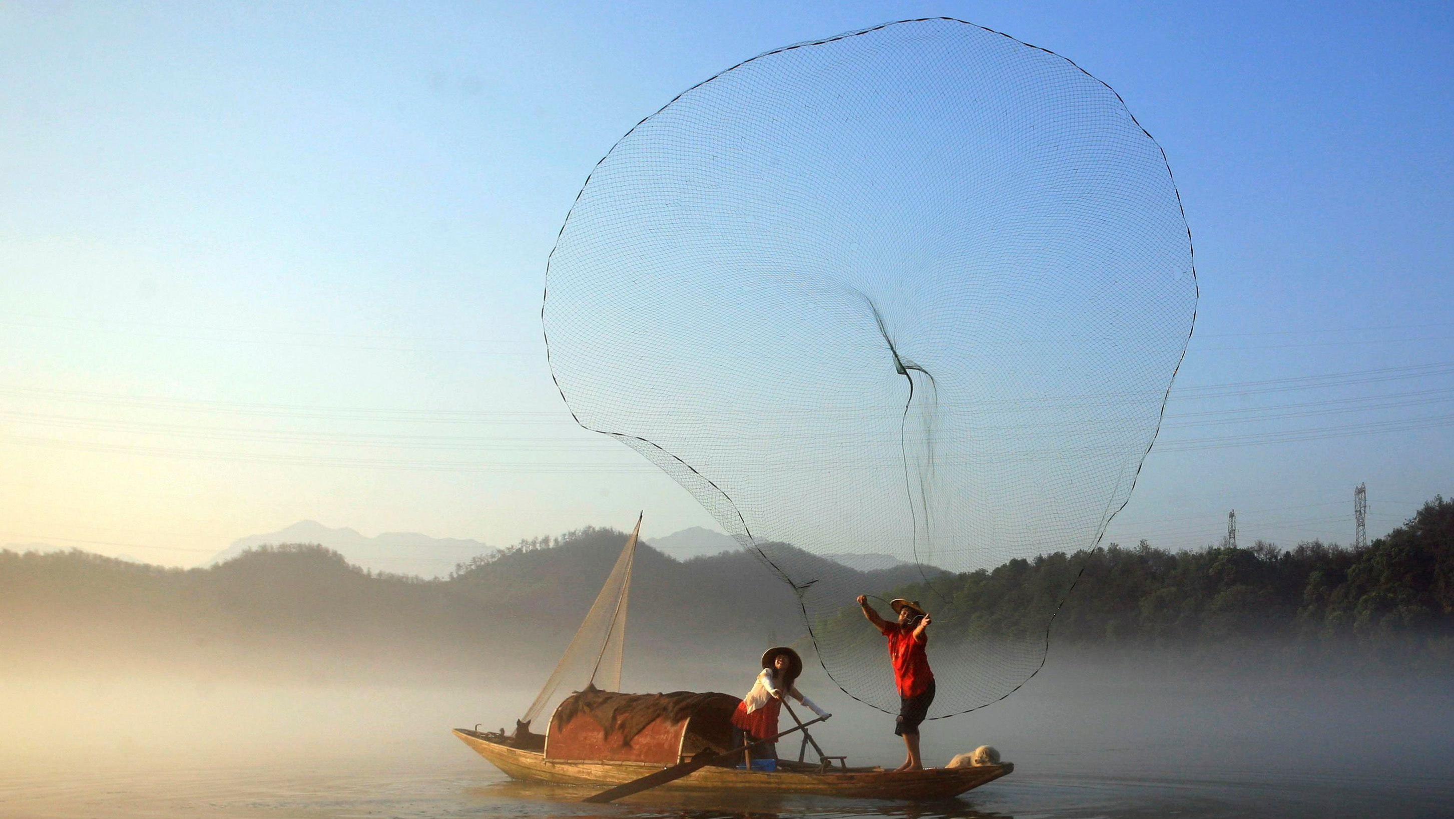 A fisherman casts his net to catch fish on Xin'an River in Jiande, Zhejiang province