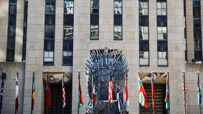 Iron throne replica in front of flags in NY.