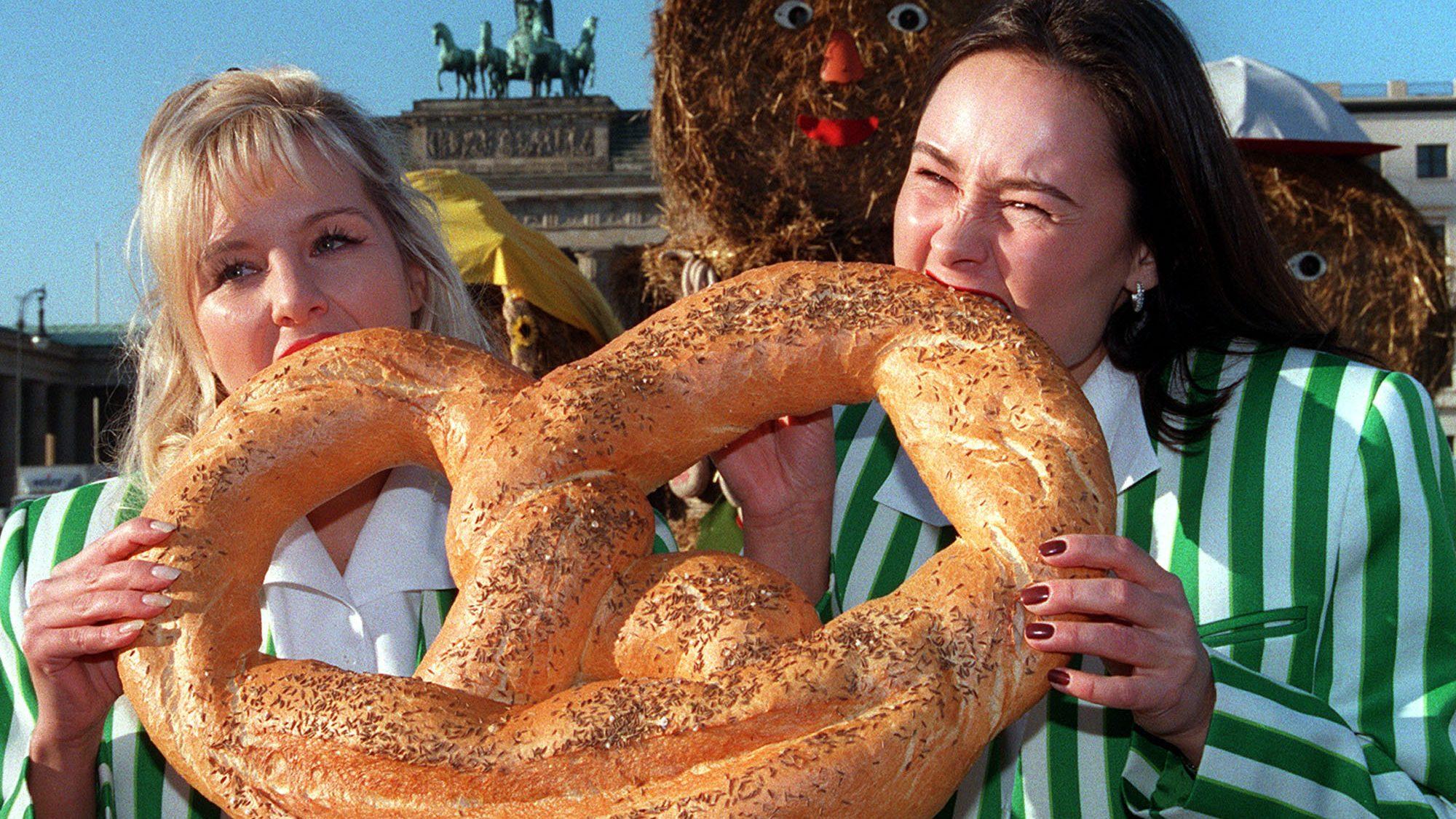 Women bite into a large pretzel
