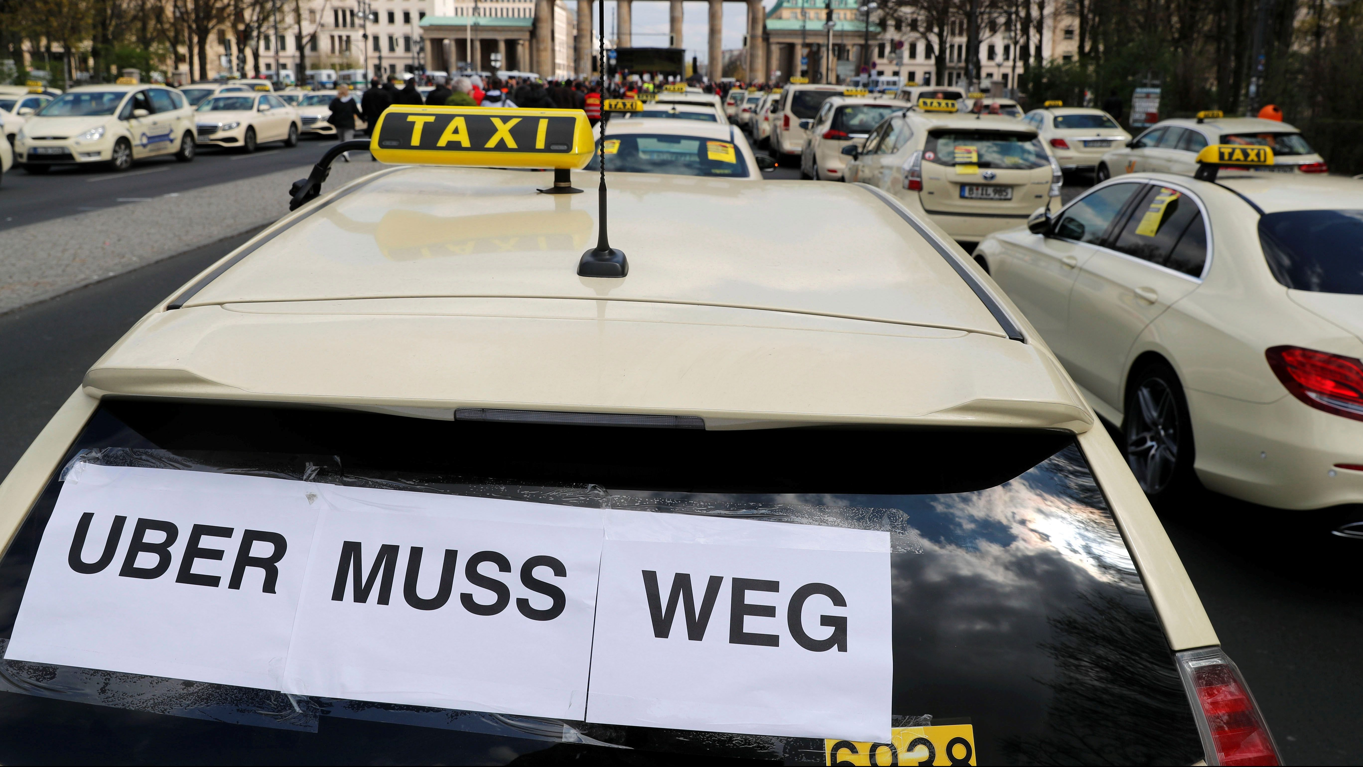 """Cars a seen during a protest of licensed taxi drivers against a planned change of the passenger transport law in Berlin, Germany, April 10, 2019. The words read """"Uber must go."""""""
