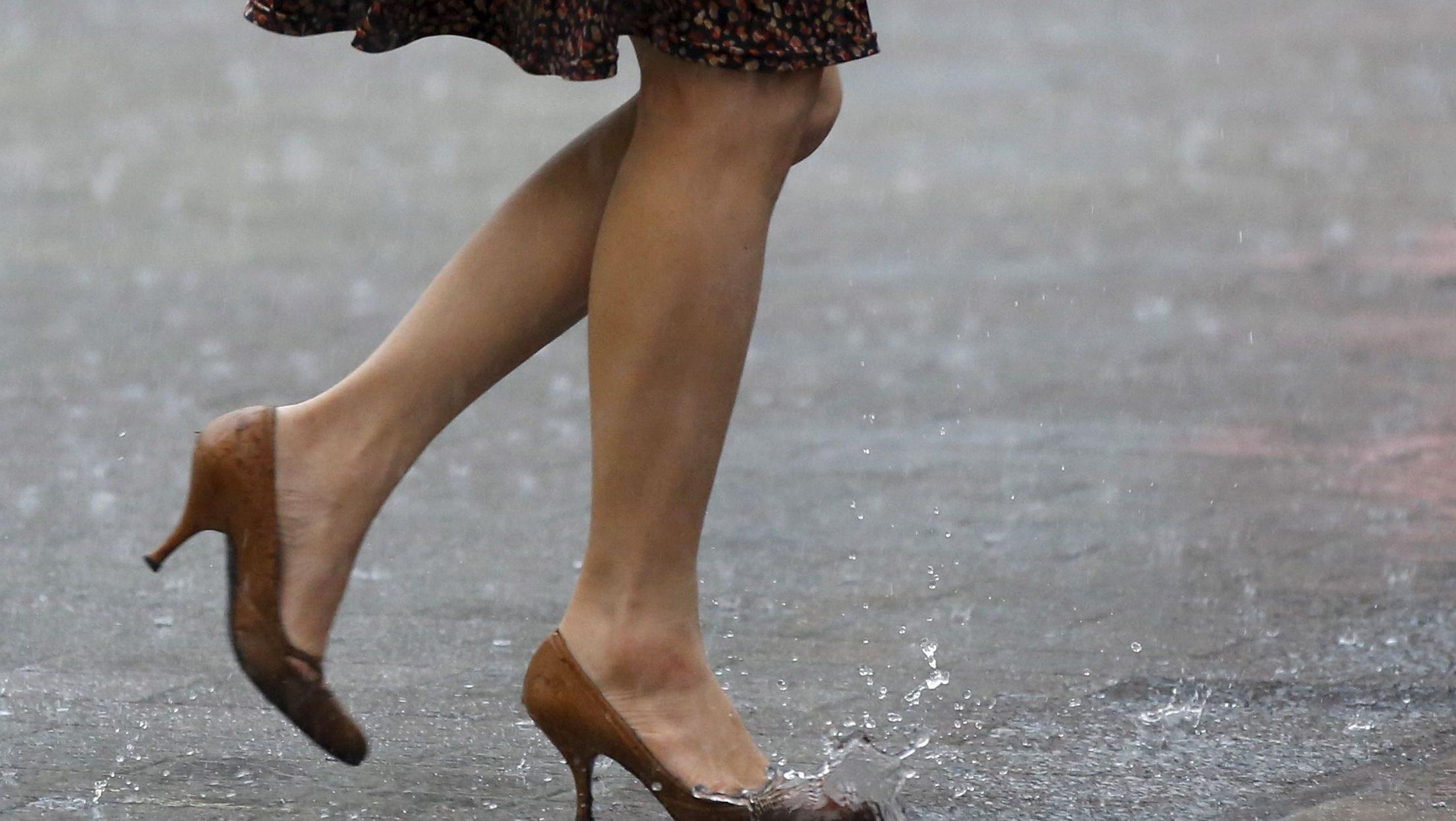 A woman walks in heavy rain