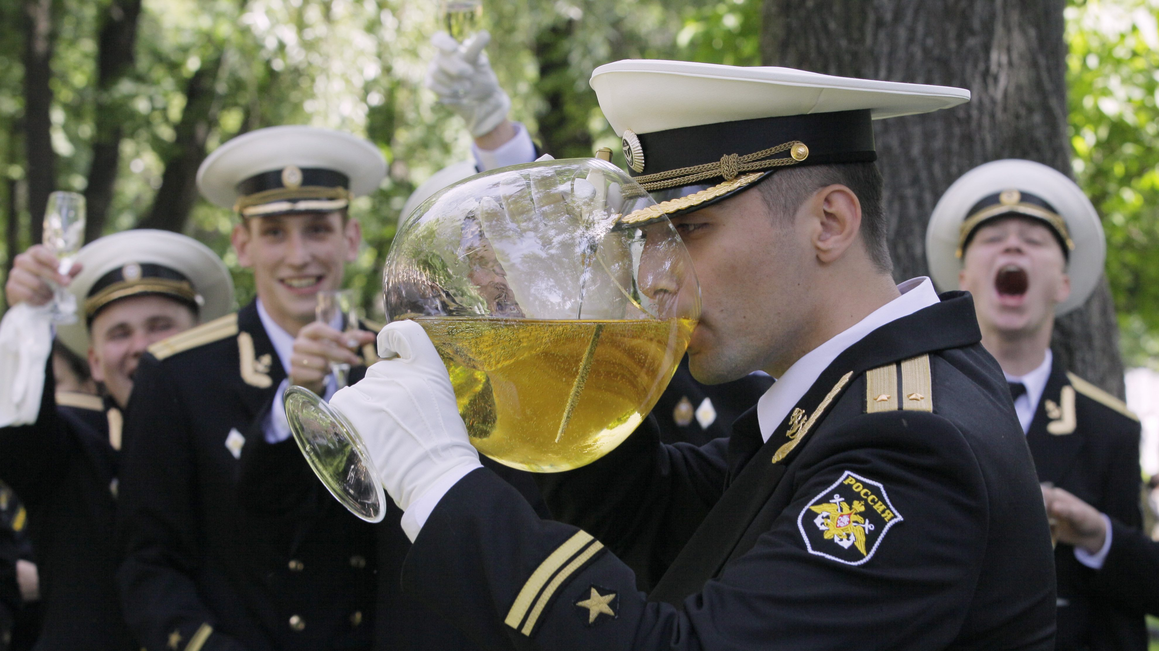 an image of a russian navy officer drinking from an enormous glass of wine