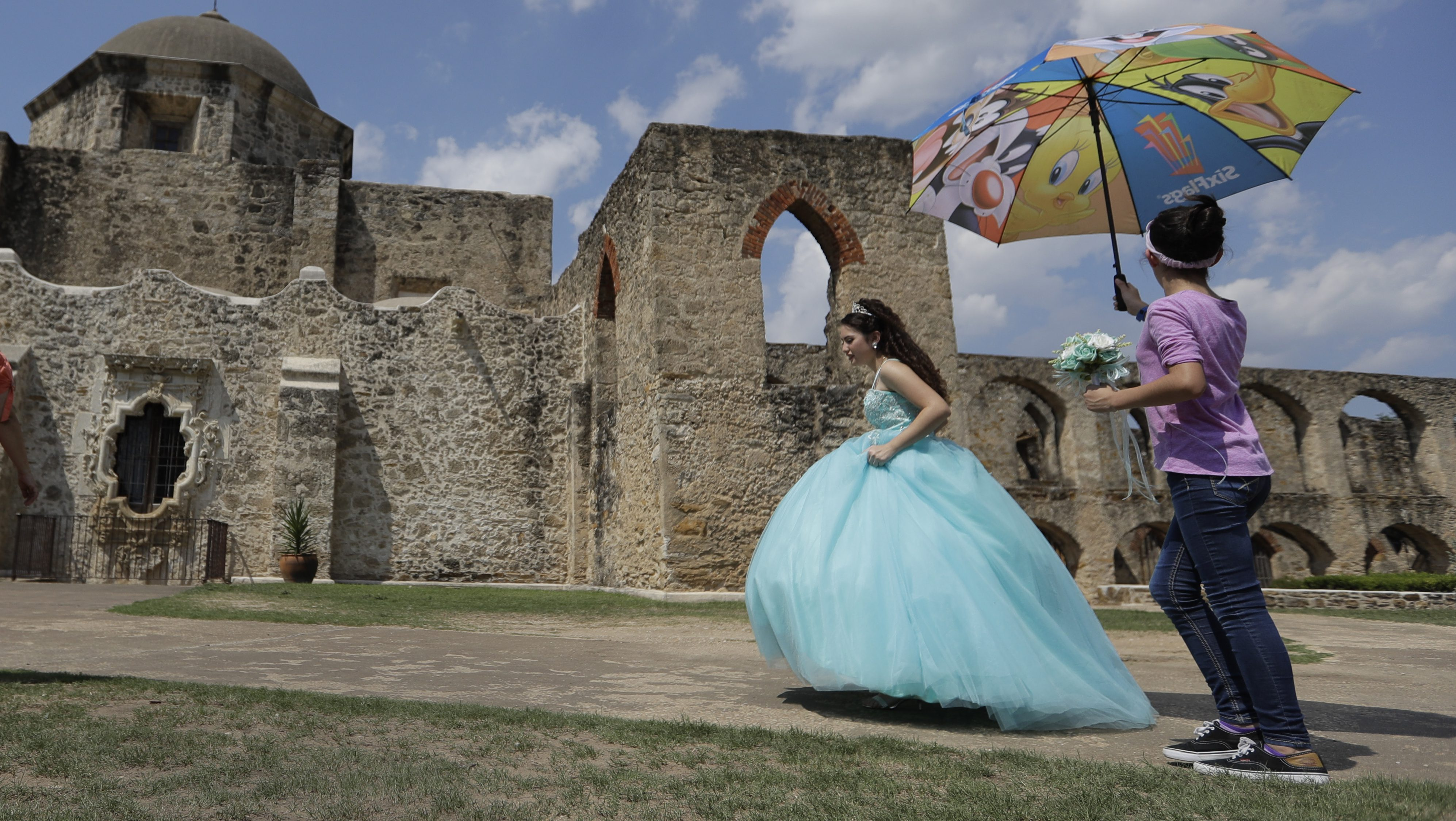 A quinceañera walks through the grounds of Mission San Jose where she was having her quinceanera photos taken,