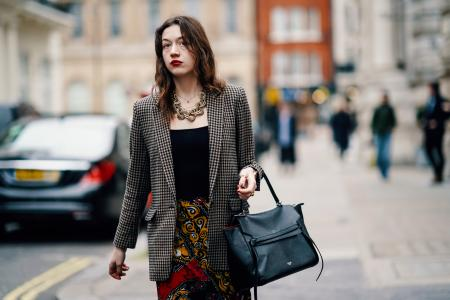 LONDON, ENGLAND - FEBRUARY 16: A guest wears a houndstooth jacket, a large necklace, a black top, a black Celine backpack, colorful floral print pants, during London Fashion Week February 2019 on February 16, 2019 in London, England. (Photo by Edward Berthelot/Getty Images)