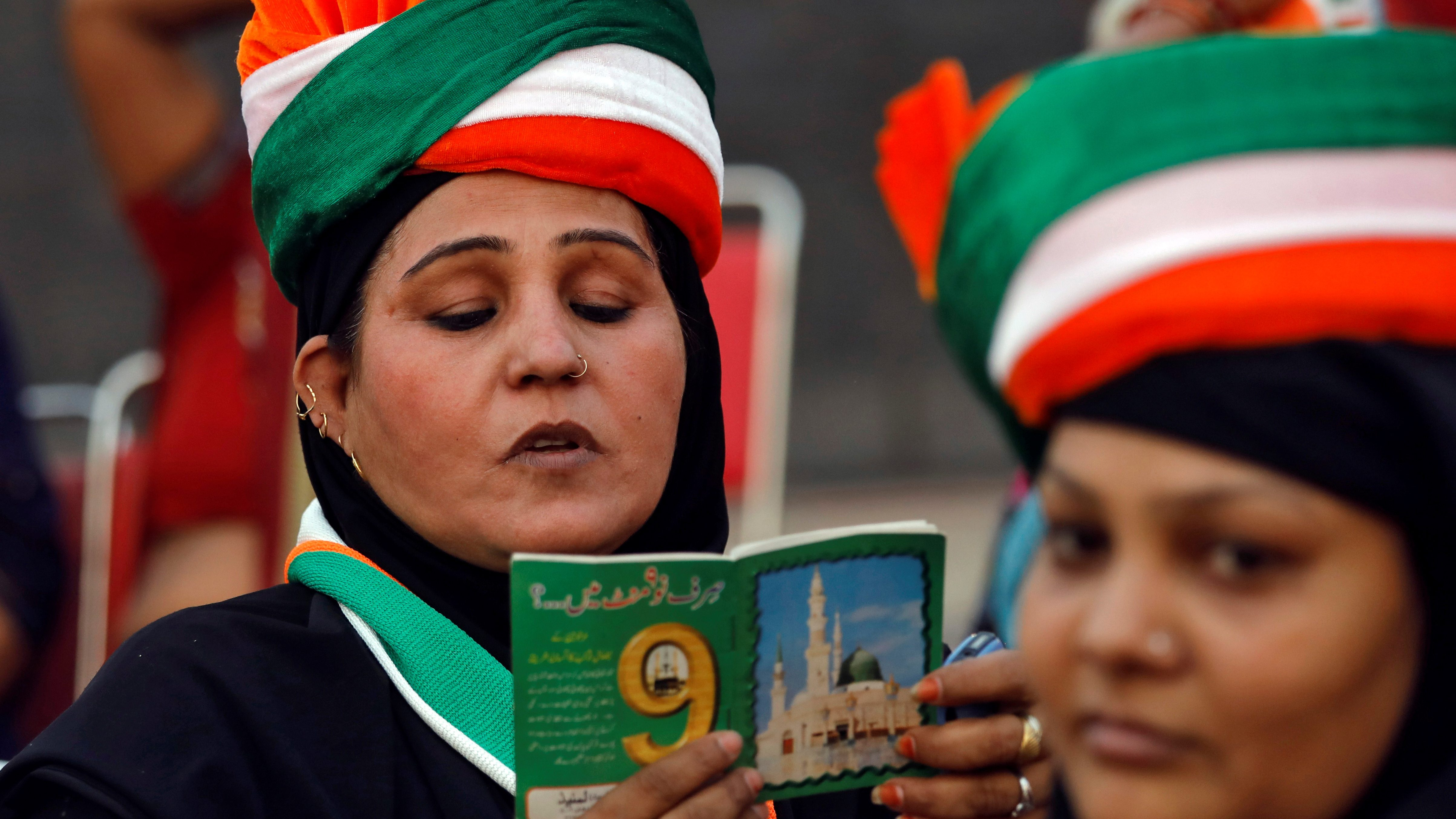 Muslim woman reads Koranic supplication as she attends an election campaign rally addressed by India's main opposition Congress party President Rahul Gandhi in New Delhi