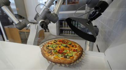 A pizza being made by a robot.