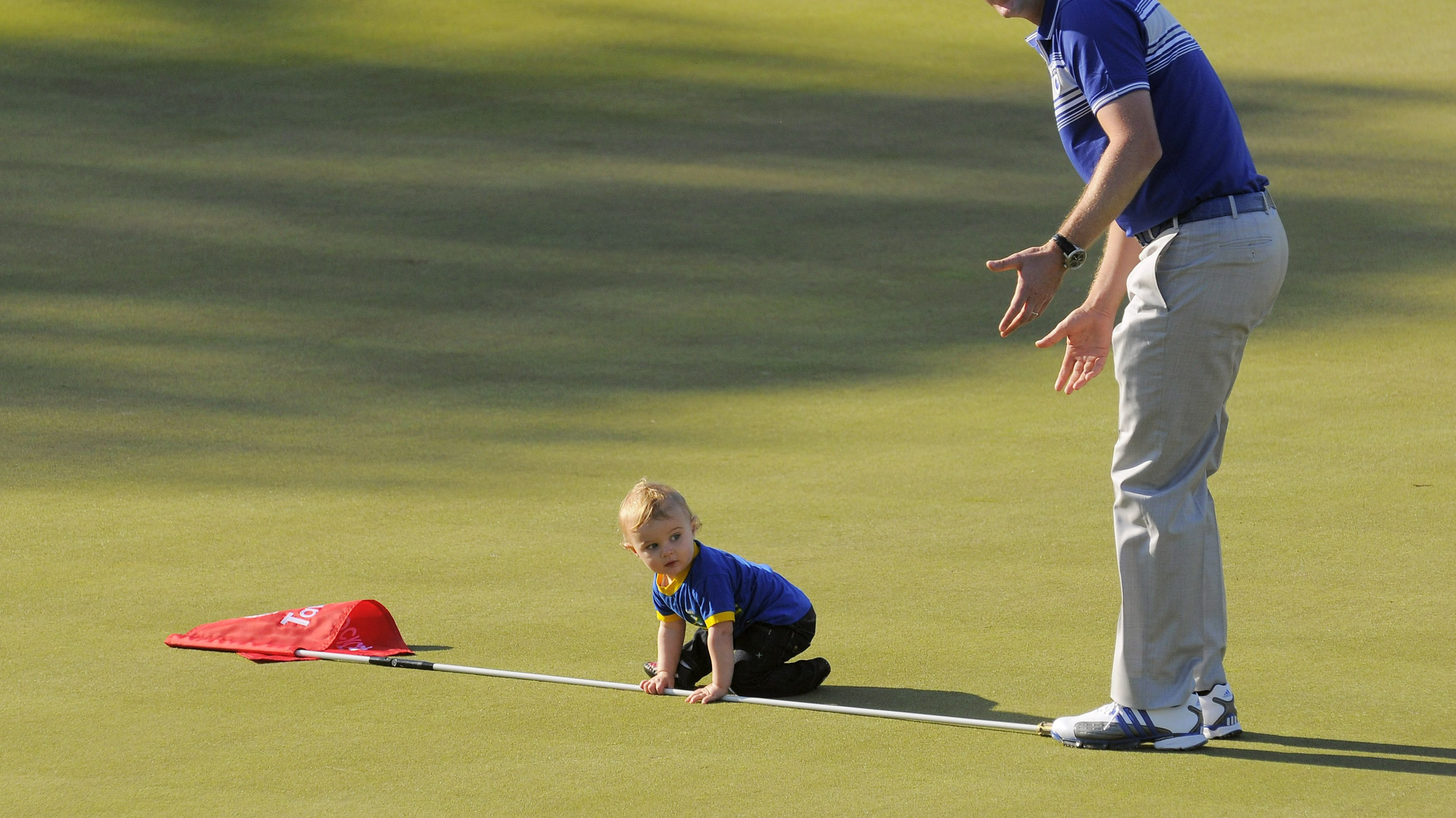 Lake Nona team member Rose laughs as his son Leo plays with the pin flag on the 18th green following the Tavistock Cup in Windermere