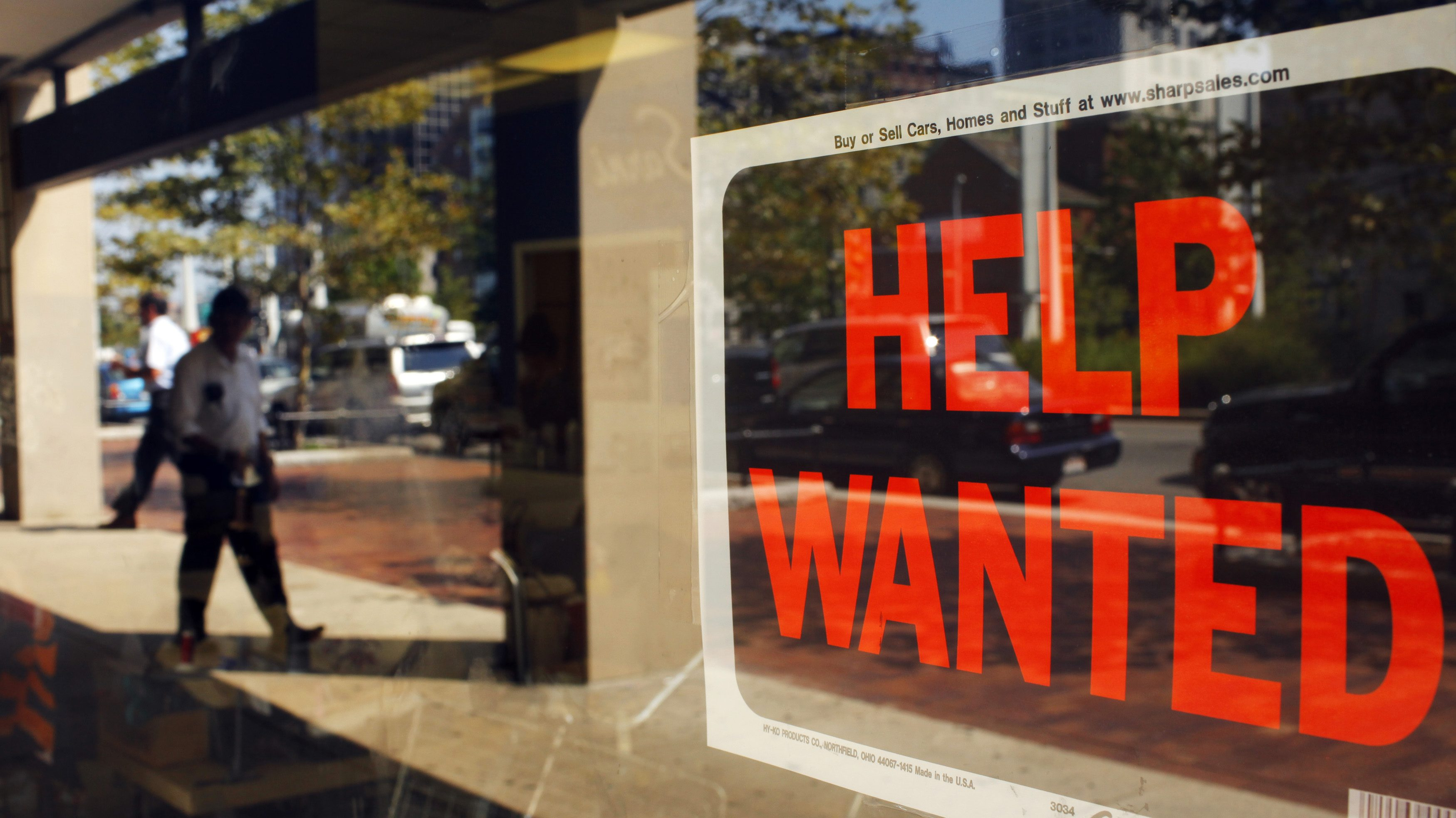 """A """"Help Wanted"""" sign in the window advertises a job opening at a dry cleaners in Boston"""