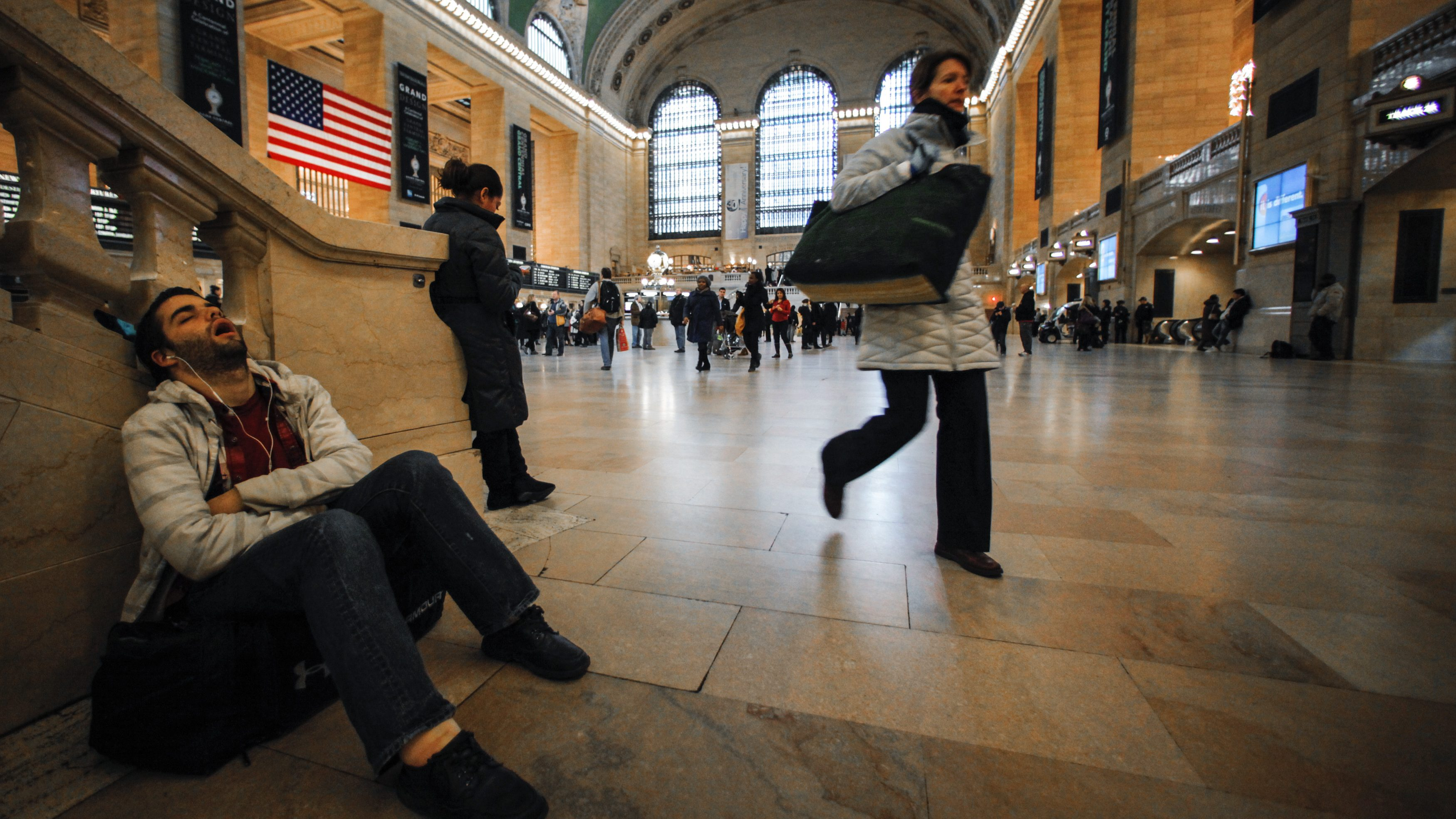 A commuter takes a nap before his train departs from the Grand Central Station in New York