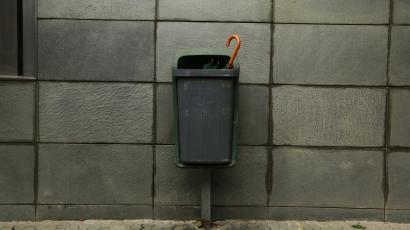 An umbrella is seen in a trash can after a rainy night in Seville