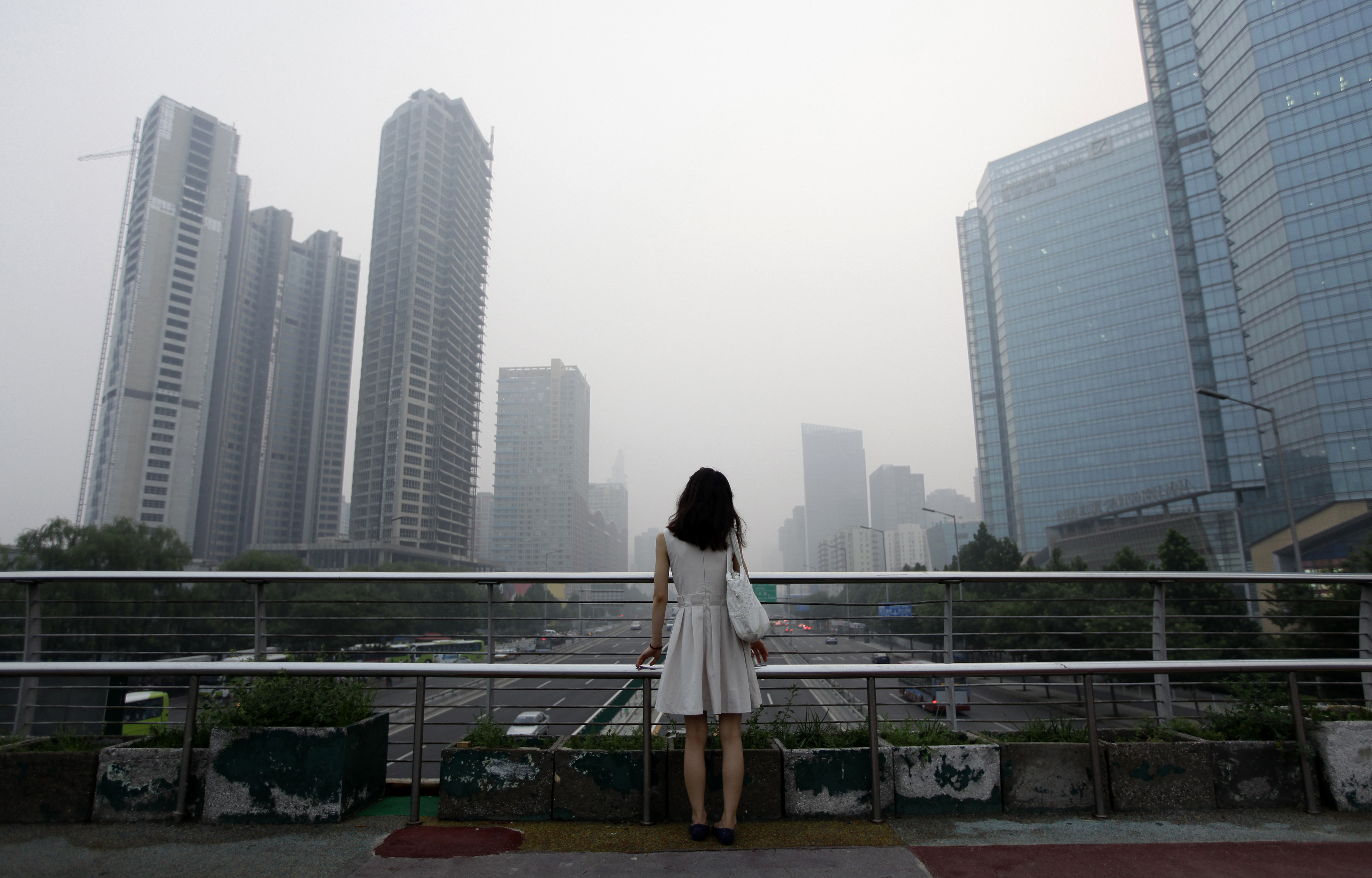 "A woman stands on an overhead bridge near the construction site of ""Kaisa Plaza"", then named ""Changan No. 8"" (L), on a hazy day in Beijing's central business district in this July 28, 2012 file picture. Struggling Chinese developer Kaisa Group plunged further into crisis on Monday as several of its bank accounts were frozen and a number of creditors sought immediate repayment of debts. REUTERS/Jason Lee/Files (CHINA - Tags: ENVIRONMENT BUSINESS) - GM1EB1D16G601"