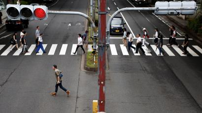 People walk on a crosswalk at a shopping district in Tokyo