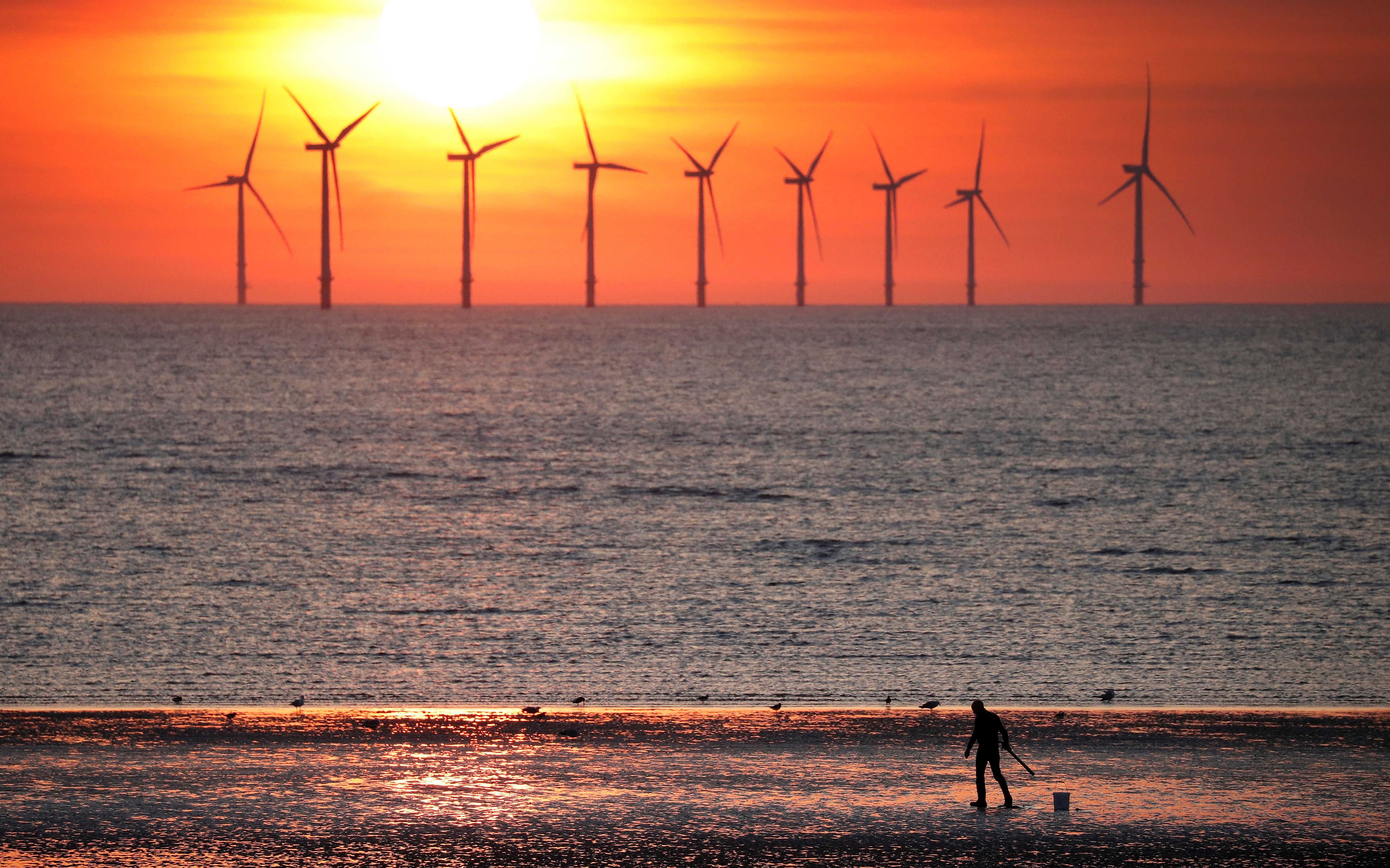 A man stands on the beach as the sun sets behind the Burbo Bank wind farm near New Brighton, Britain, May 22, 2018.