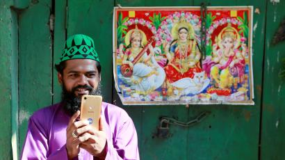 A Muslim man takes photographs with his mobile as he stands next to a picture of Hindu deities during a religious procession to mark Eid-e-Milad-ul-Nabi, or birthday celebrations of Prophet Mohammad, in the old quarters of Delhi
