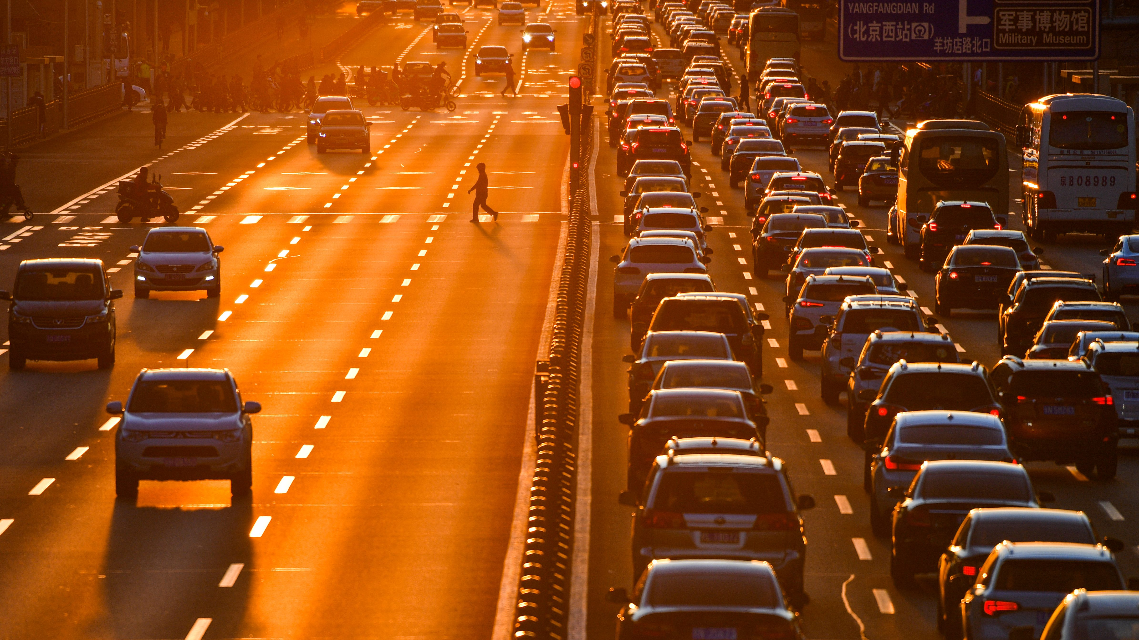 Pedestrian walks on a crossing next to cars in the traffic on a main road during sunset in Beijing