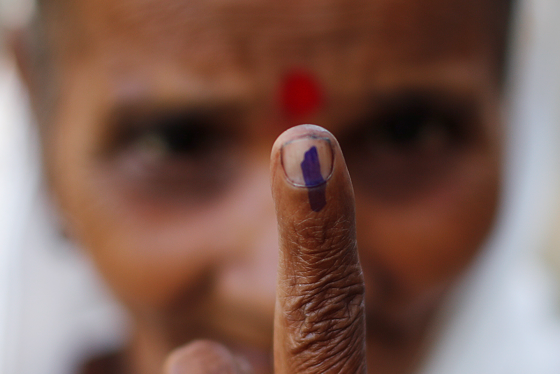 A woman shows her ink-marked finger after casting her vote at a polling station in Majuli
