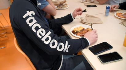 A man wearing a branded sweatshirt eats at Facebook's headquarters in London
