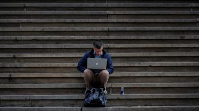 A man uses his Apple laptop on the steps of Federal Hall on Wall St. in the financial district of New York