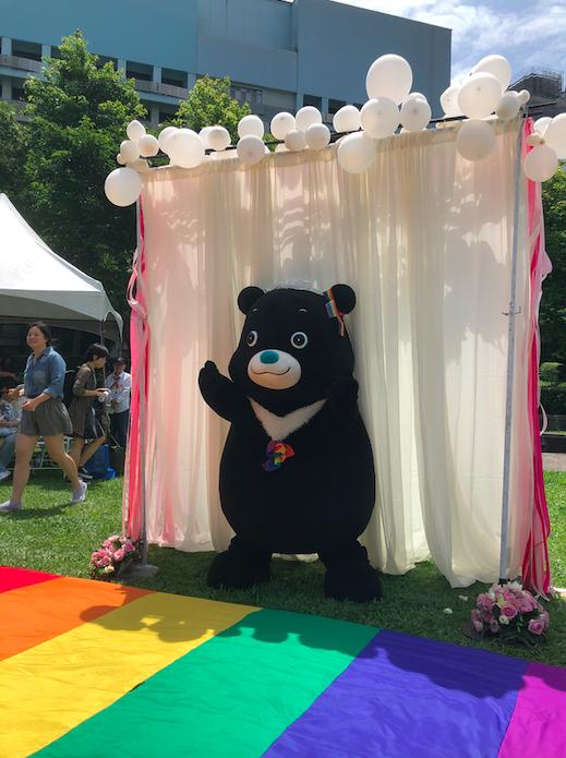 Taipei's mascot, a black bear named Bravo, alone on the rainbow aisle.