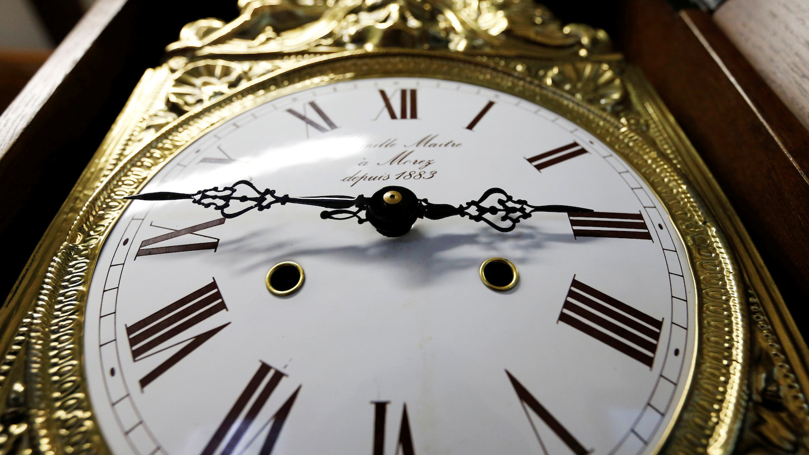 The hands of a clock are pictured on a wall clock in a watchmaker's shop in Bordeaux