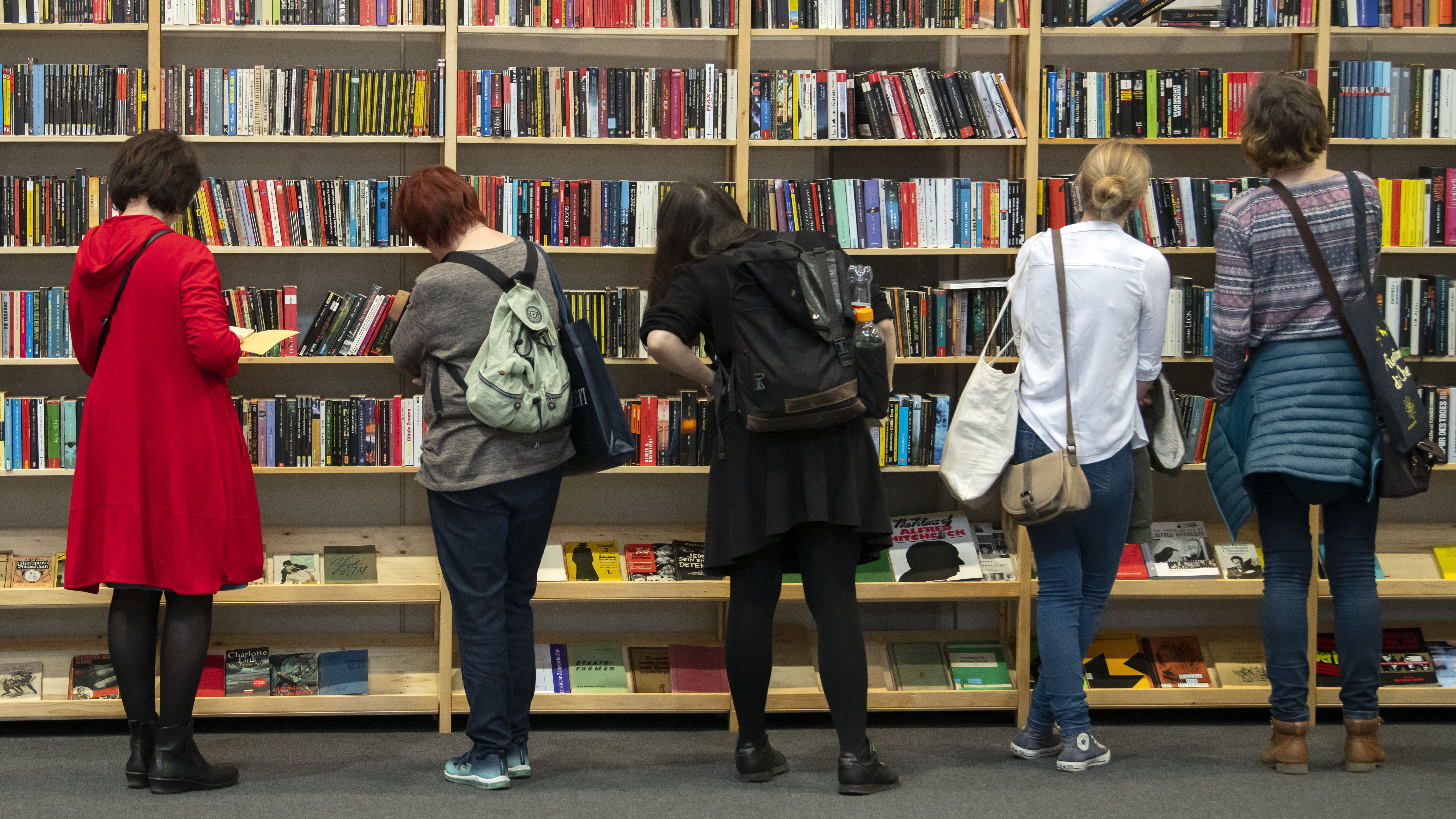 People looking at book shelves at a store.