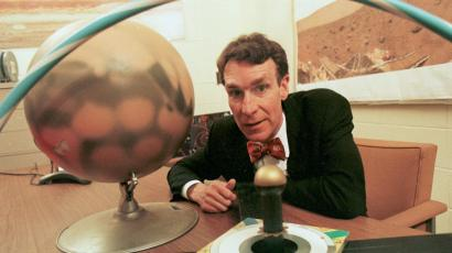 An image of Bill Nye sitting at a desk with a globe from the 90s.
