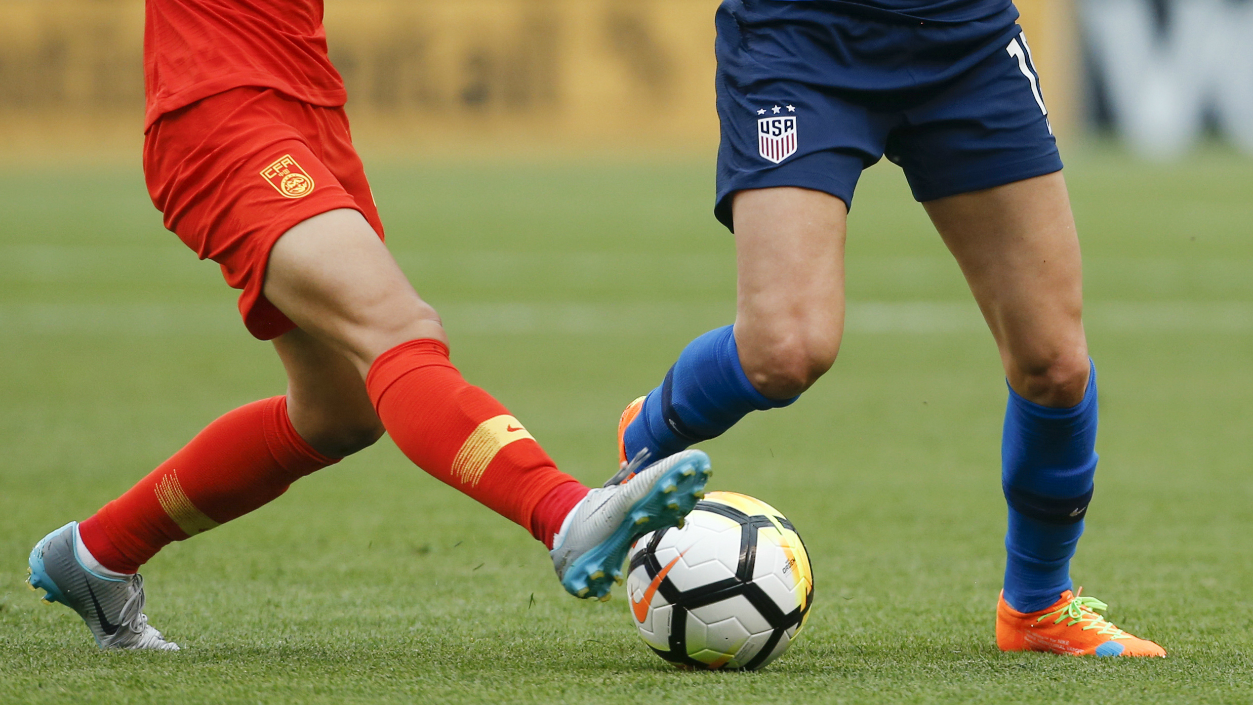 Chinese and US soccer players fight for a soccer ball.