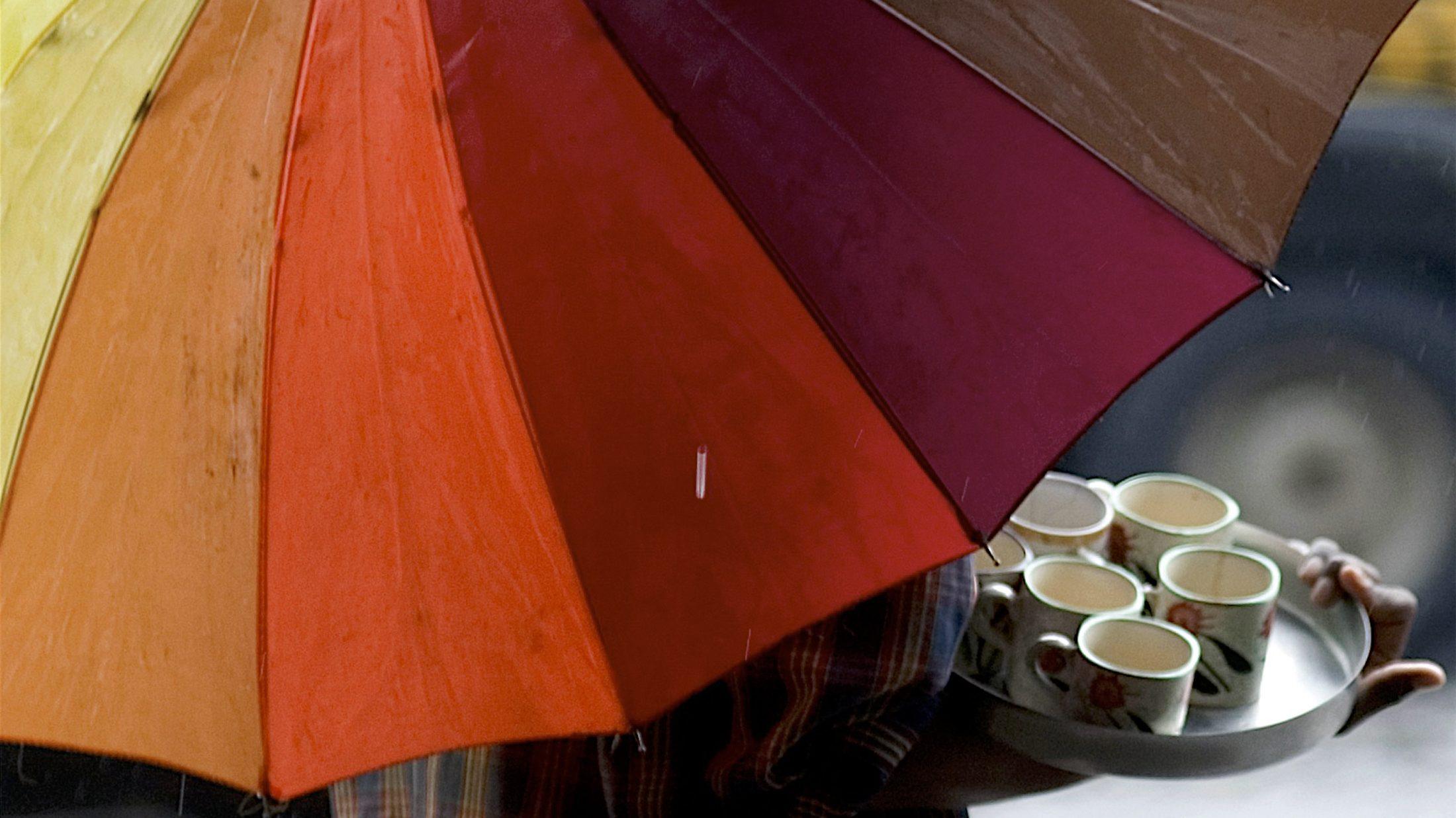 Tea vendor holds umbrella at roadside in Mumbai