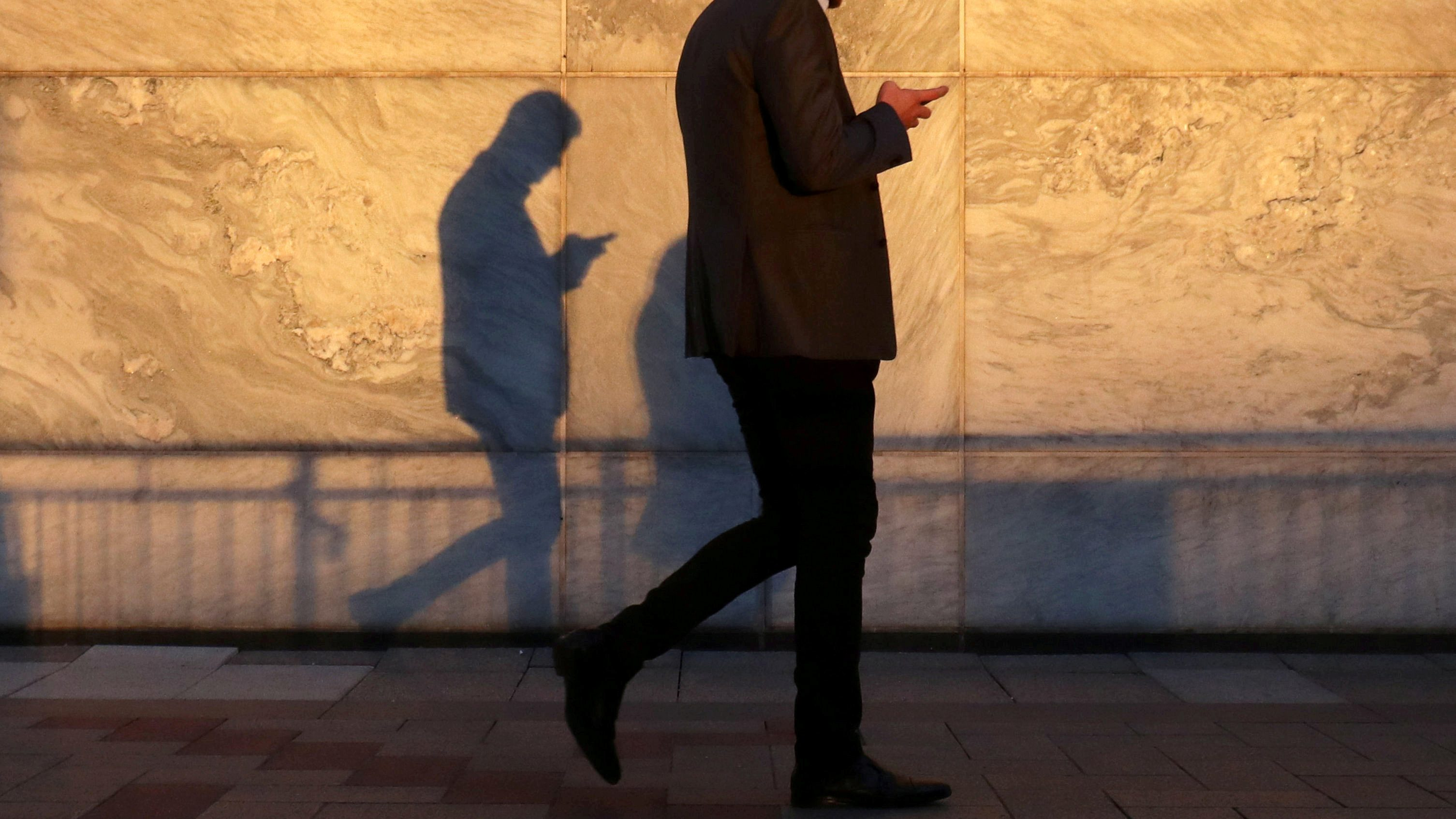 A man's shadow is visible as he walks holding a smartphone and looking down.
