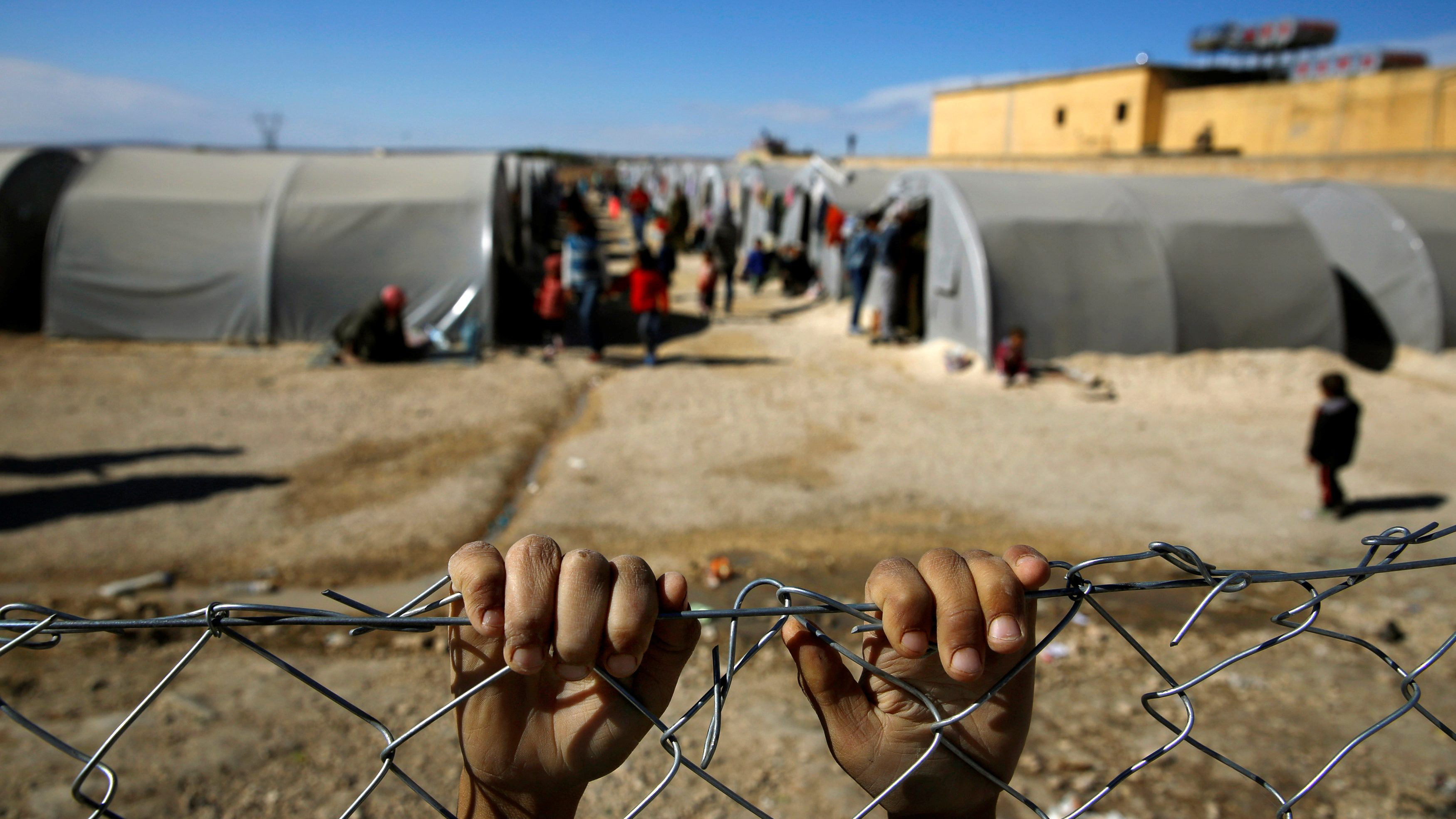 hands of a refugee boy grabbing the fence of a refugee camp in Turkey
