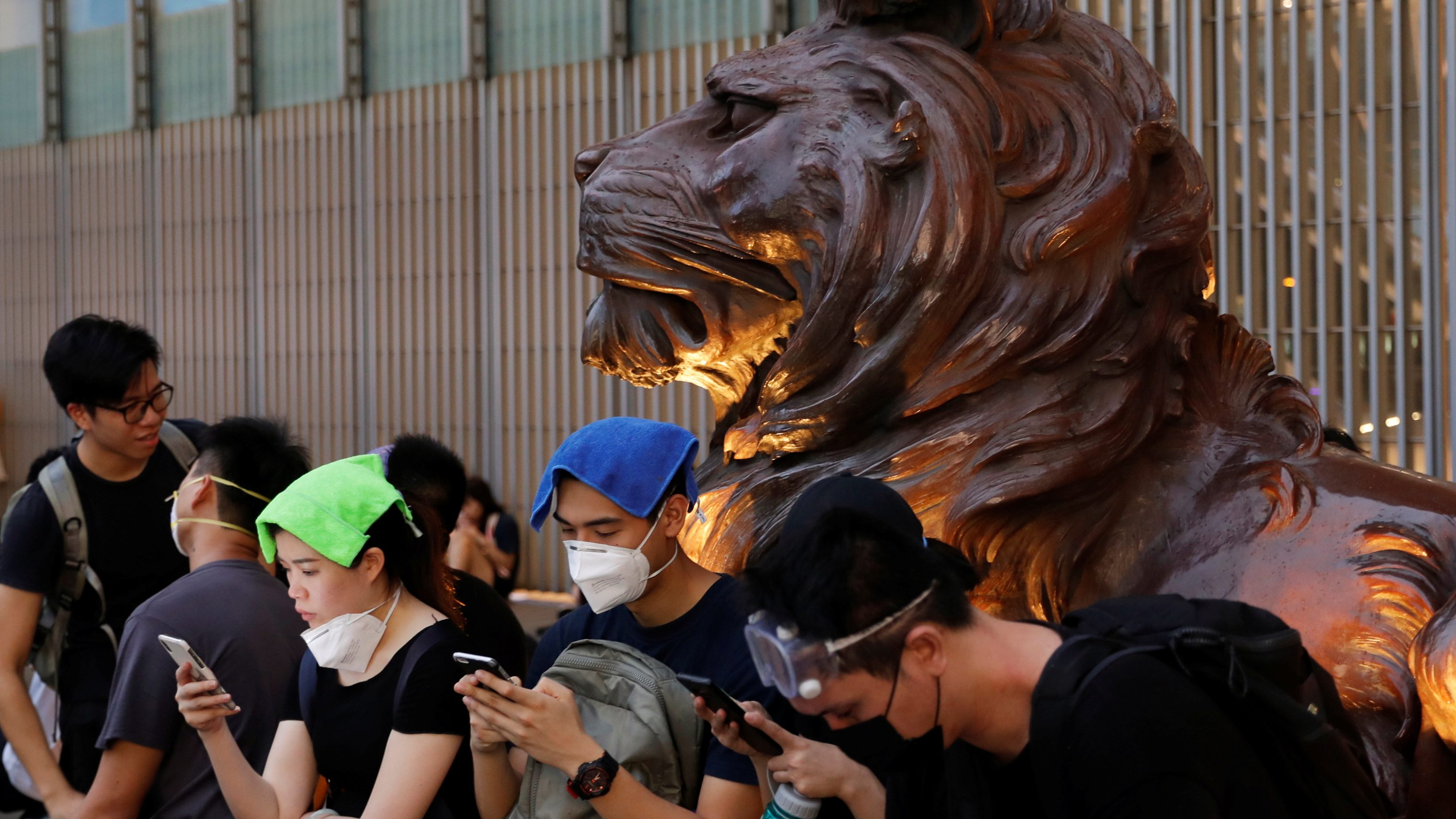 Protesters use their mobile phones as they stand outside HSBC bank headquarters during a demonstration against a proposed extradition bill in Hong Kong, China June 12, 2019.