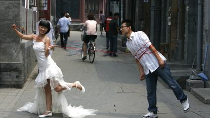 A Chinese couple pose for a wedding photo on a busy alleyway or 'hutong' in Beijing July 7, 2008.