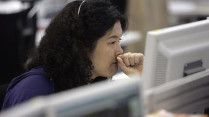A call centre personnel presses her fist to her mouth at an online brokerage company in Tokyo