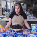 Bon Appétit test kitchen's Claire Saffitz stands in front of various Oreo cookie packages.