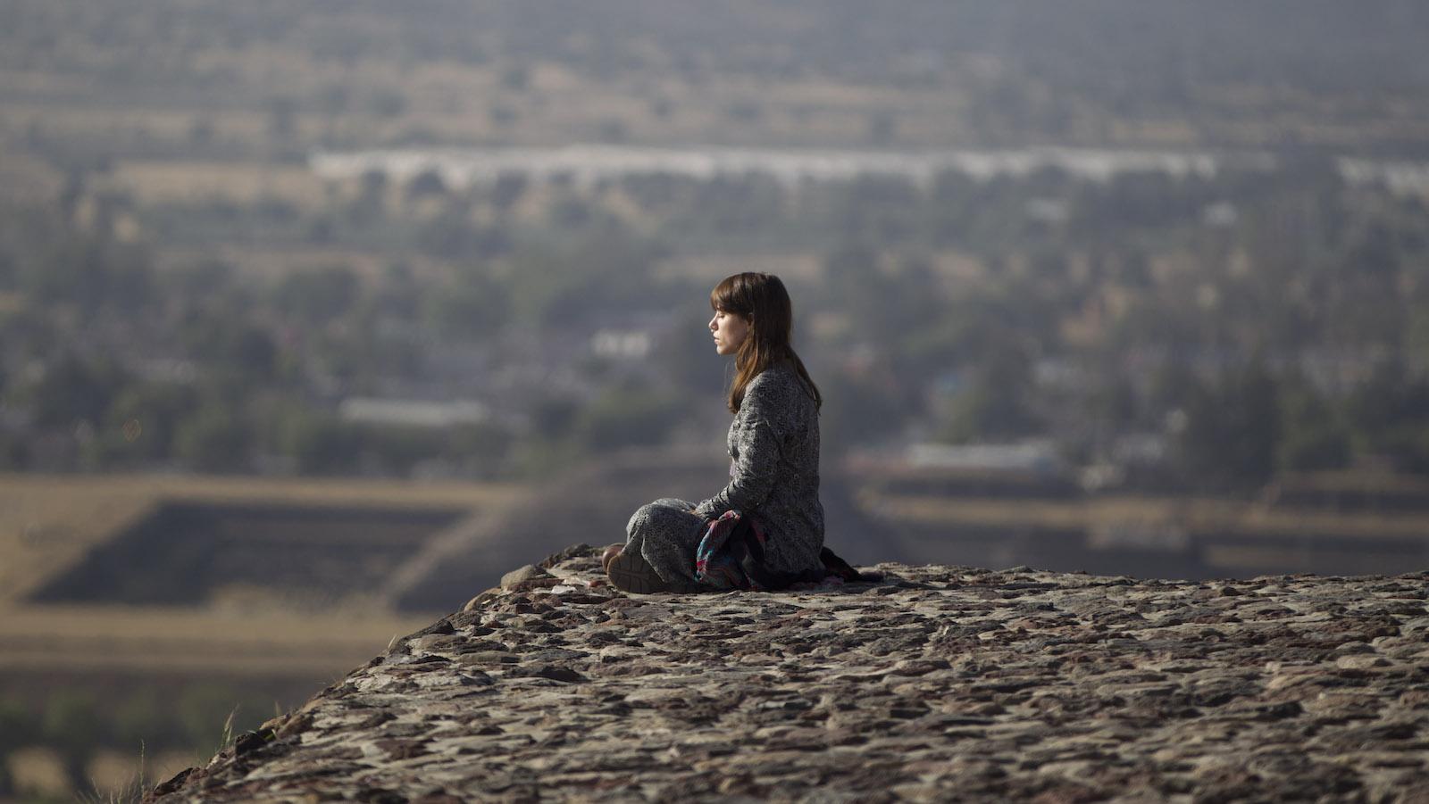 woman meditates on mountain