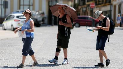 A tourist uses an umbrella to protect himself from the sun, as a heatwave hits Spain, in Ronda