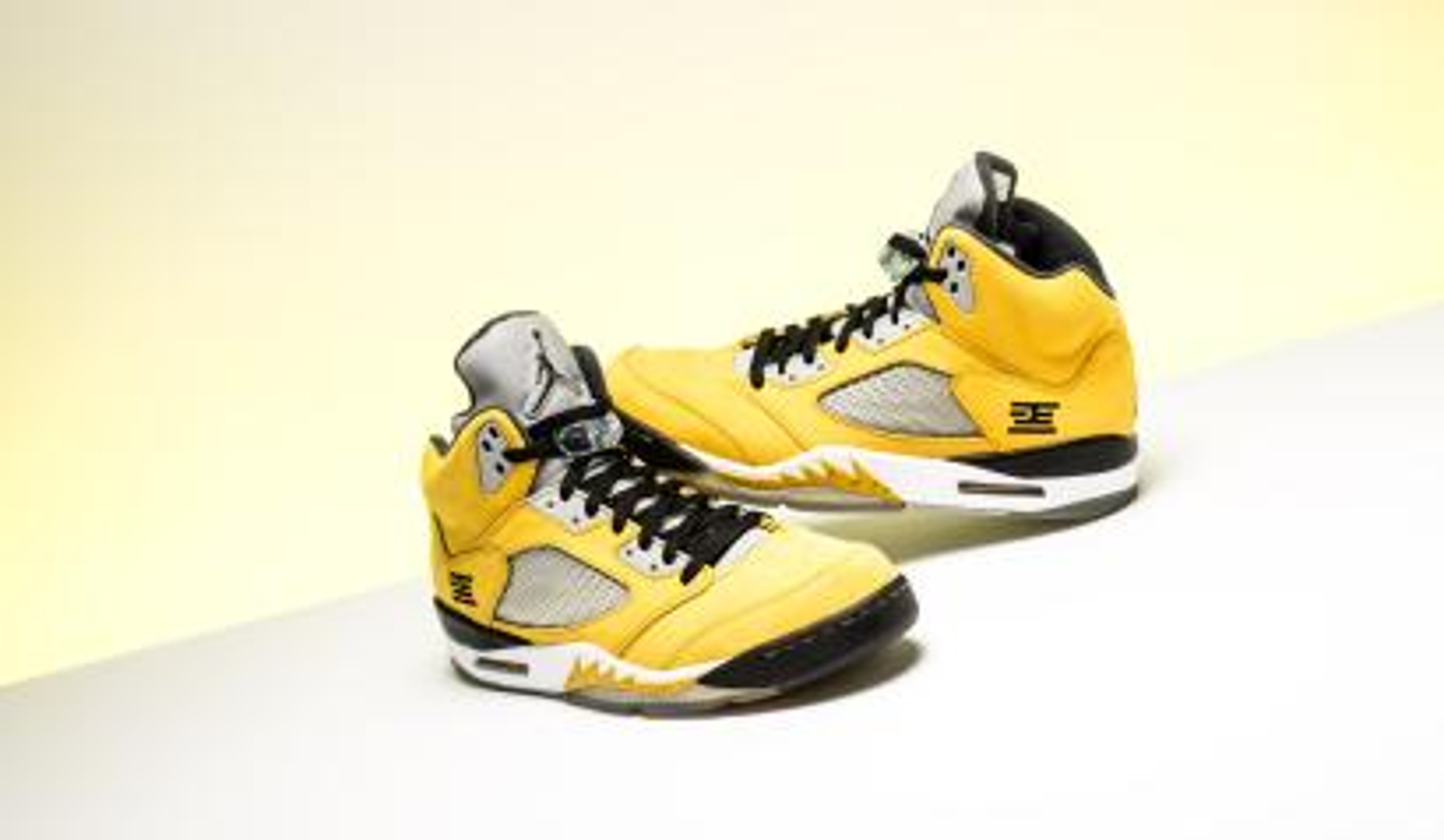 A pair of yellow Nike Air Jordan 5s