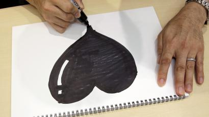 Django Co., Ltd. Director Shigetaka Kurita writes a pictograph during an interview at his office in Tokyo. The Japanese creator of the first emoji wanted to add nuance to mobile phone messages